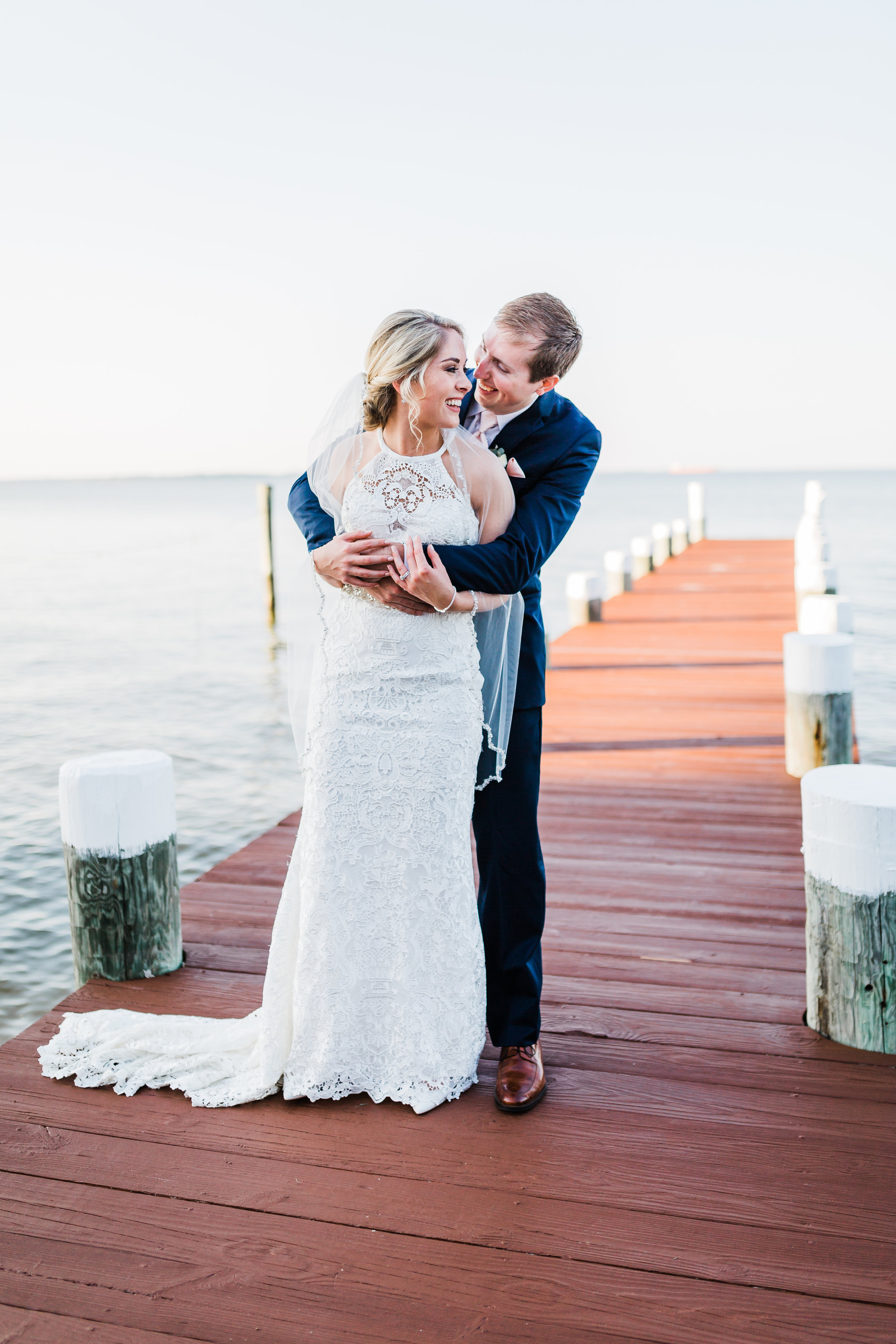 bride and groom laughing together on dock in pasadena maryland