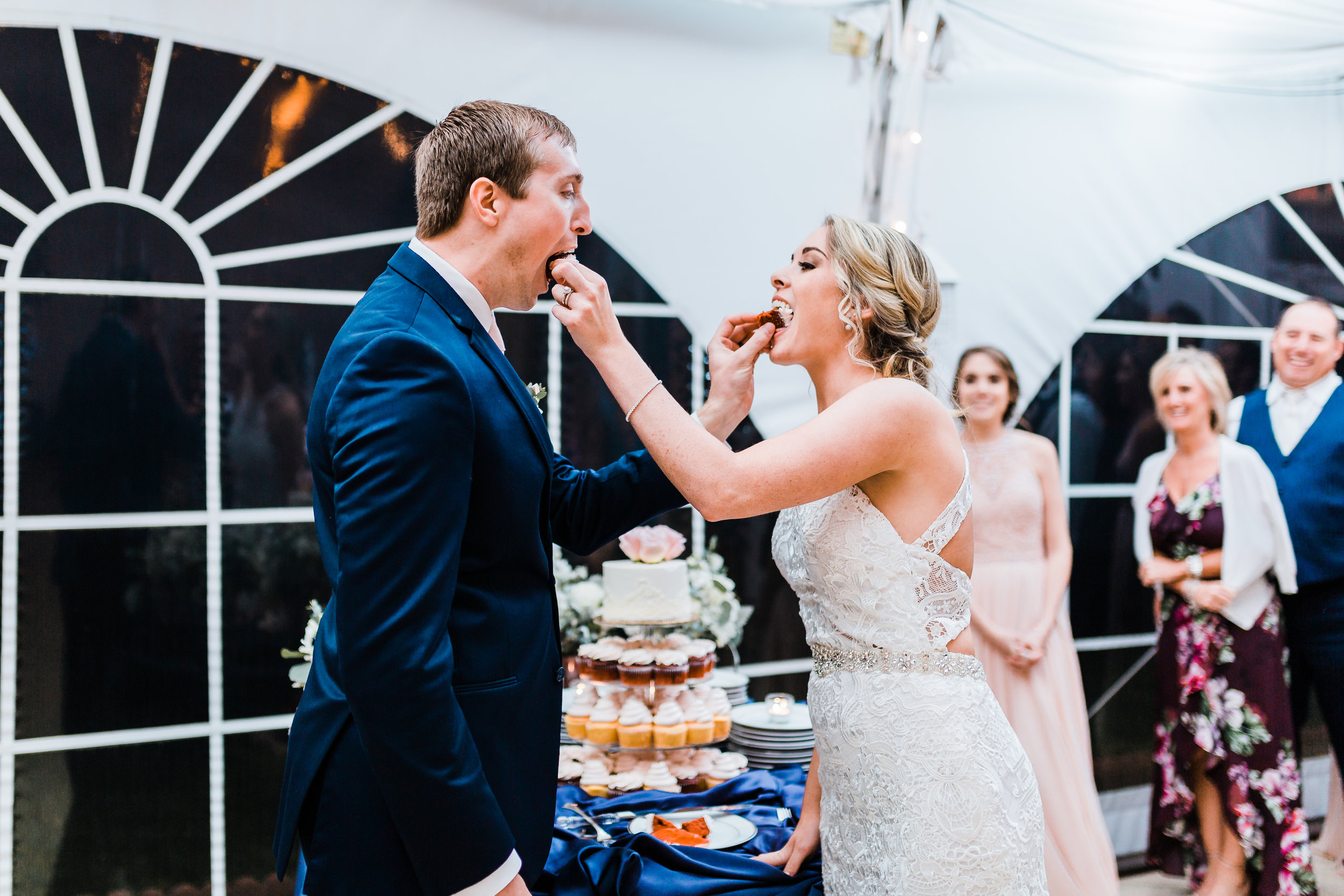 maryland couple feeding each other their cake - md wedding photographer - waterfront wedding venue