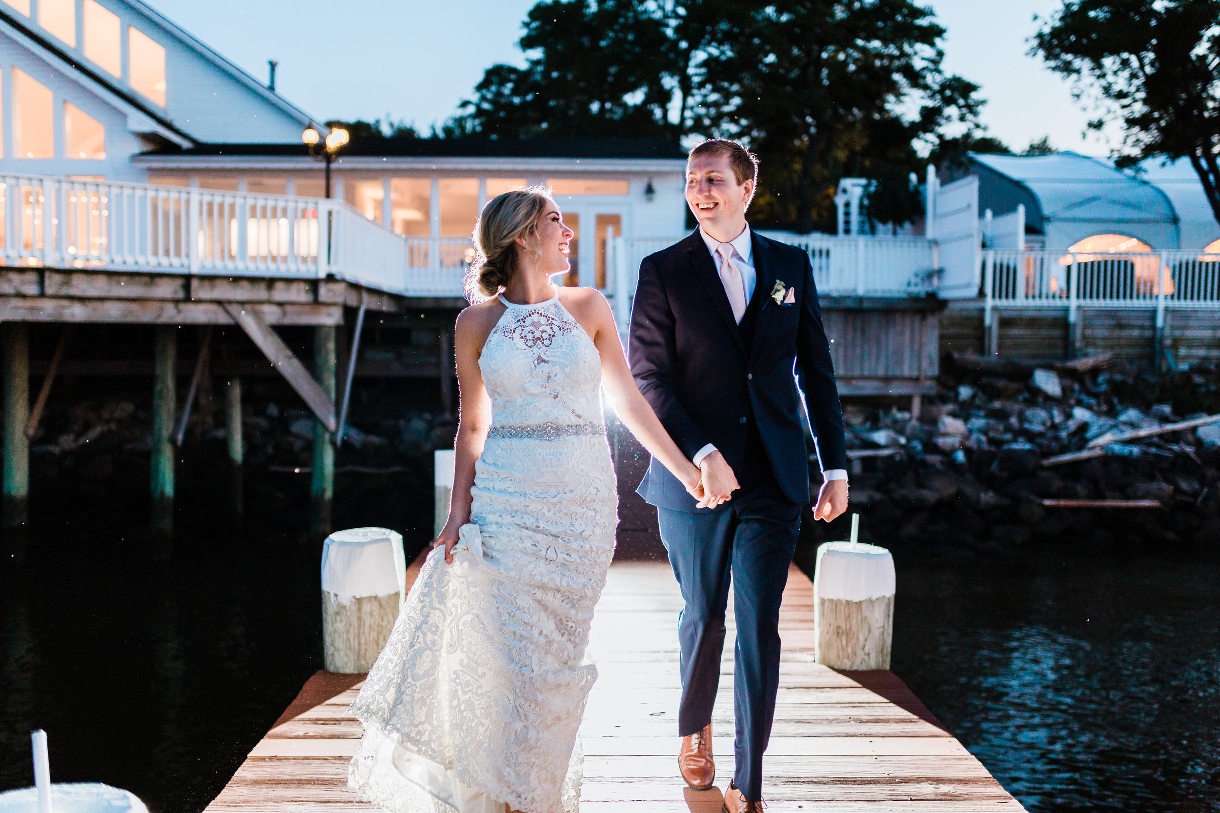 bride and groom running and laughing together - celebrations at the bay - best maryland wedding photographer