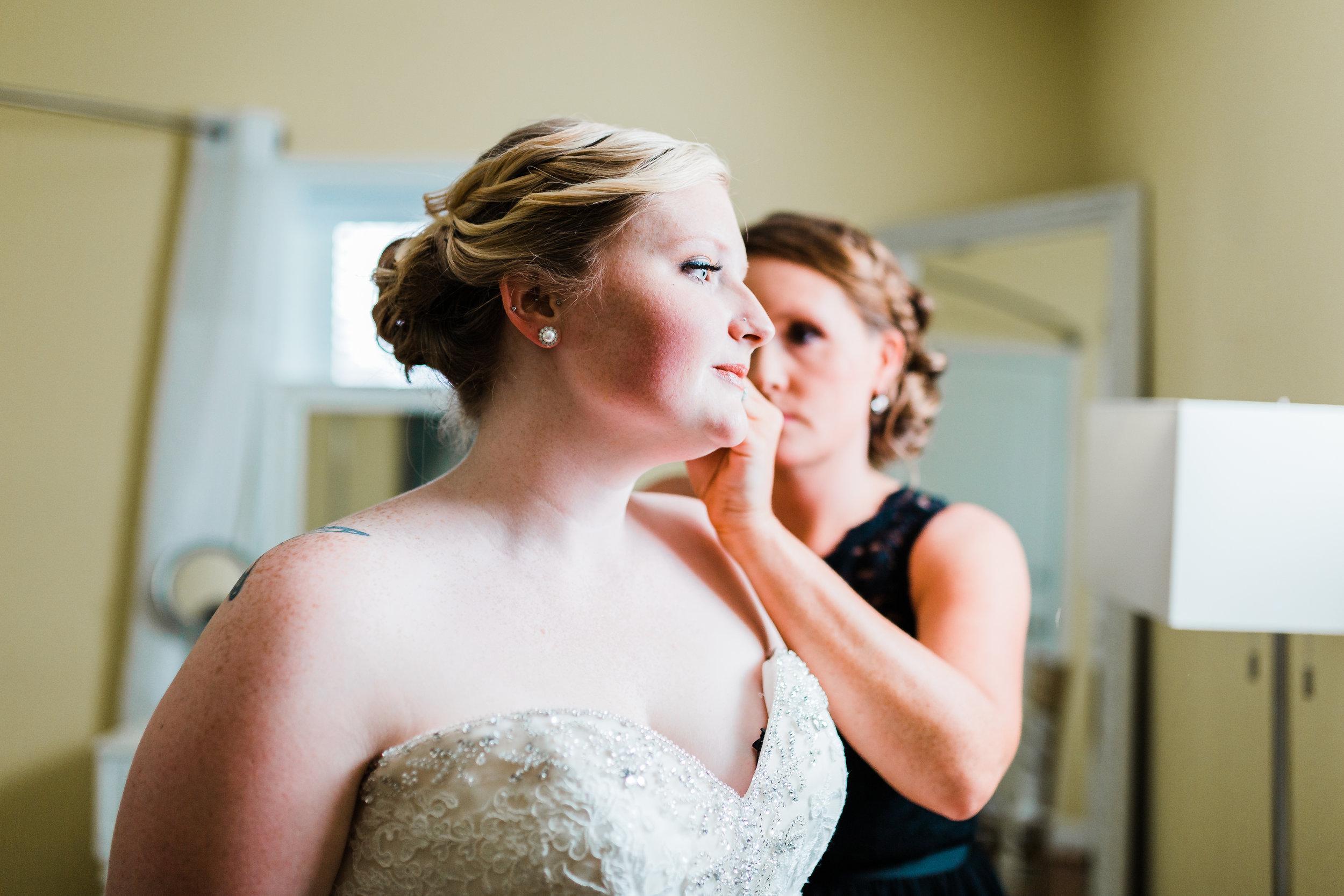 bride putting her earrings on in pasadena md - kurtz's beach weddings - best md wedding photo and video