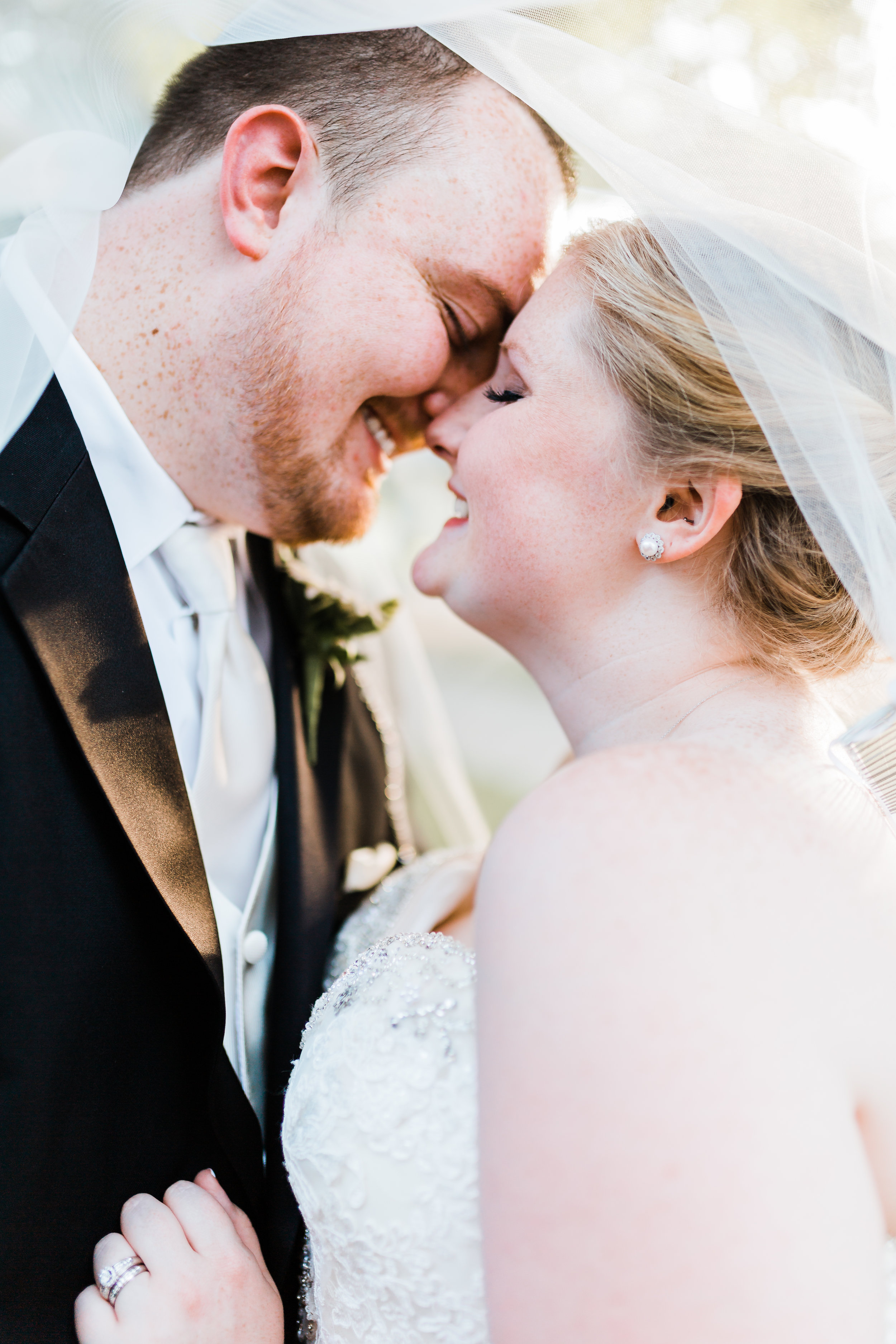 bride and groom snuggle under veil - wedding inspo - black and red wedding ideas