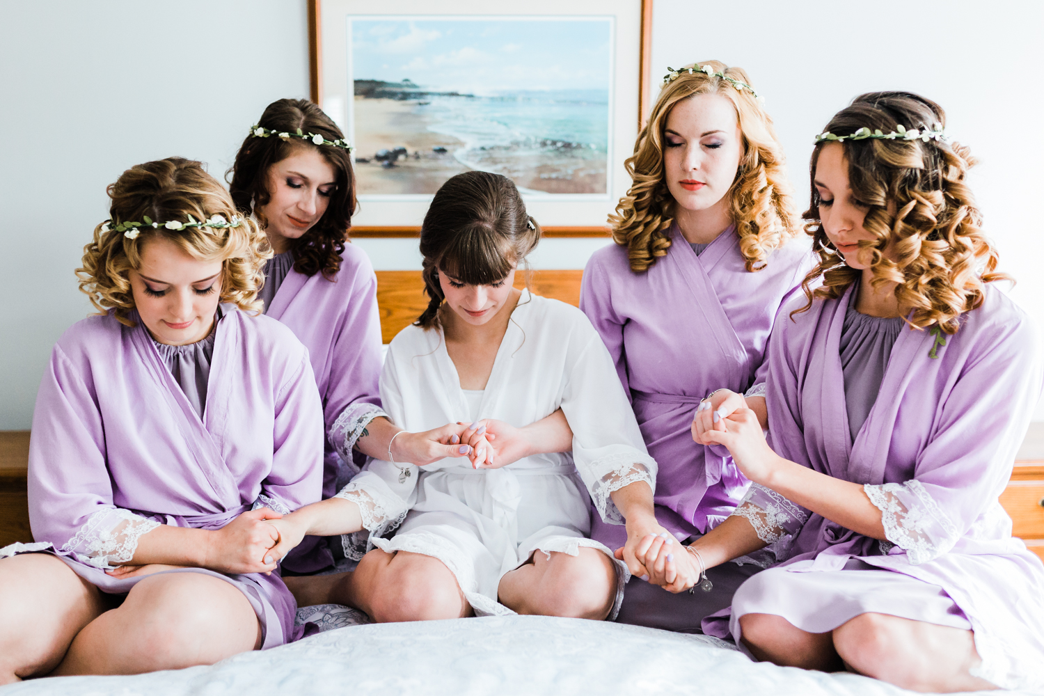 bride saying a prayer with her bridesmaids on her wedding day in maryland - best md wedding photographer