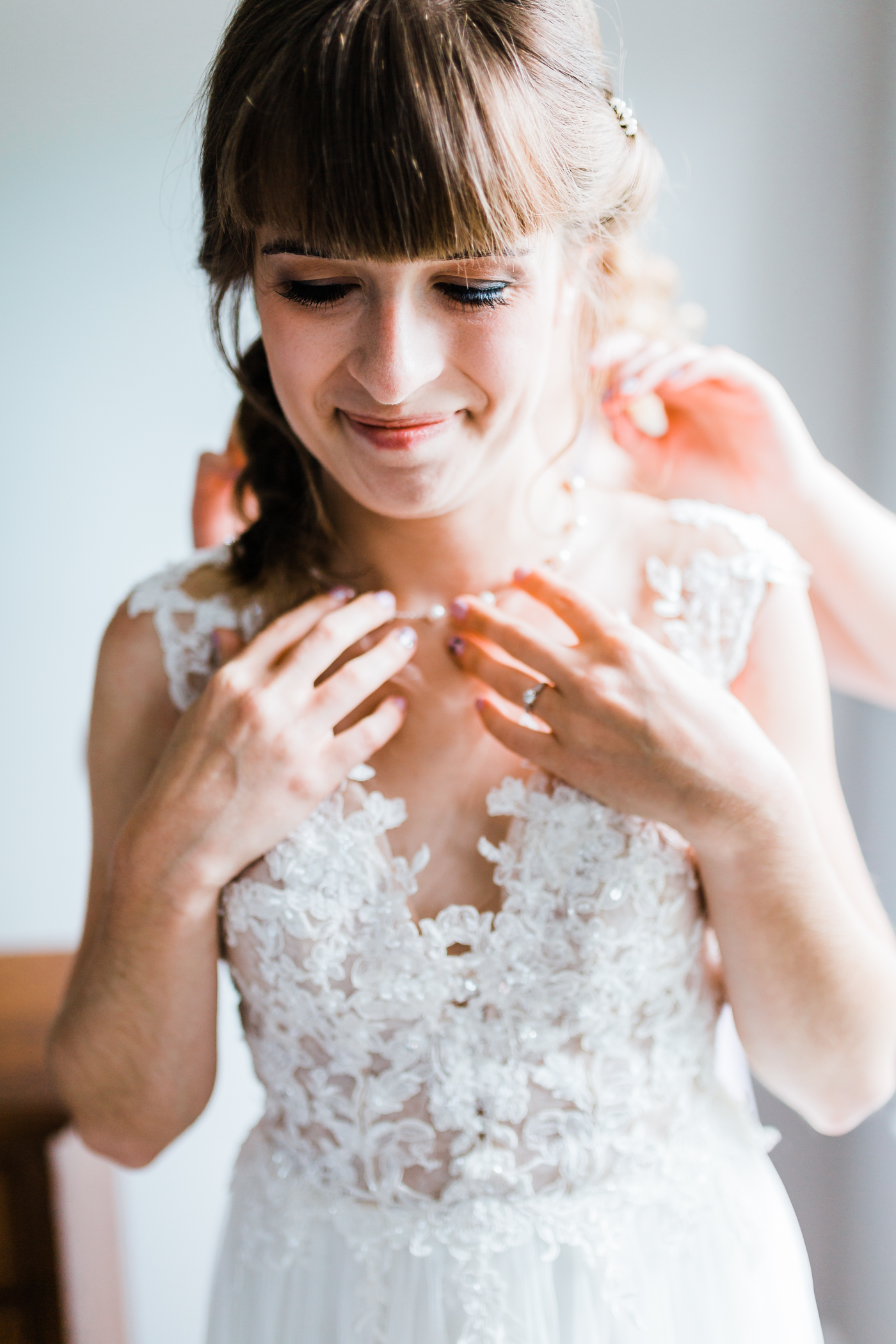 bride putting on her pearl necklace in maryland