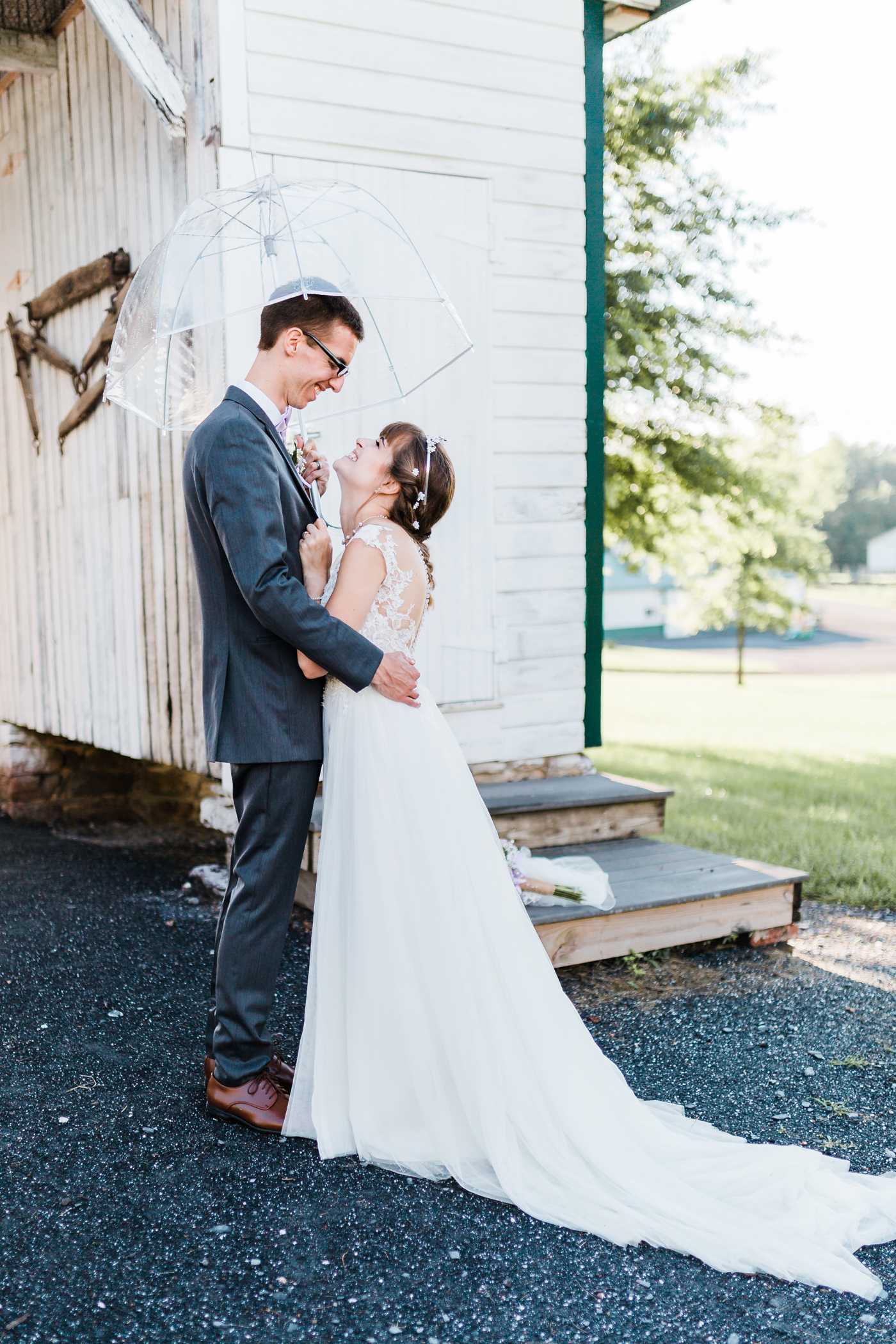 bride and groom together under umbrella after a little rain - rainy wedding inspo - bride and groom with clear umbrella - maryland wedding photographer