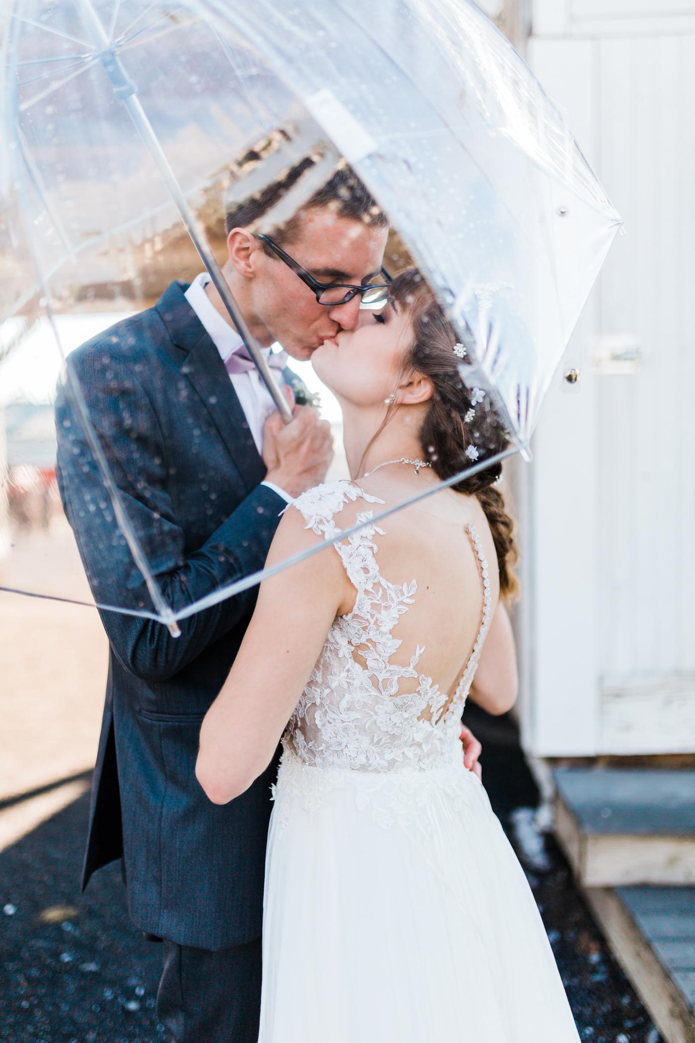 bride and groom share a romantic kiss under an umbrella - top maryland wedding photographer