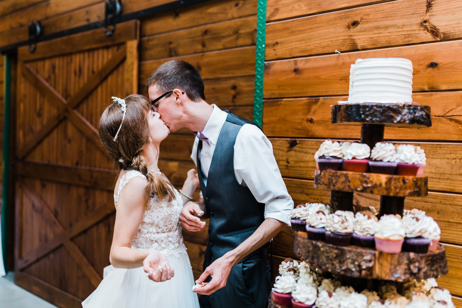 bride and groom kiss after their cake cutting near their cupcake tower - maryland wedding photographer