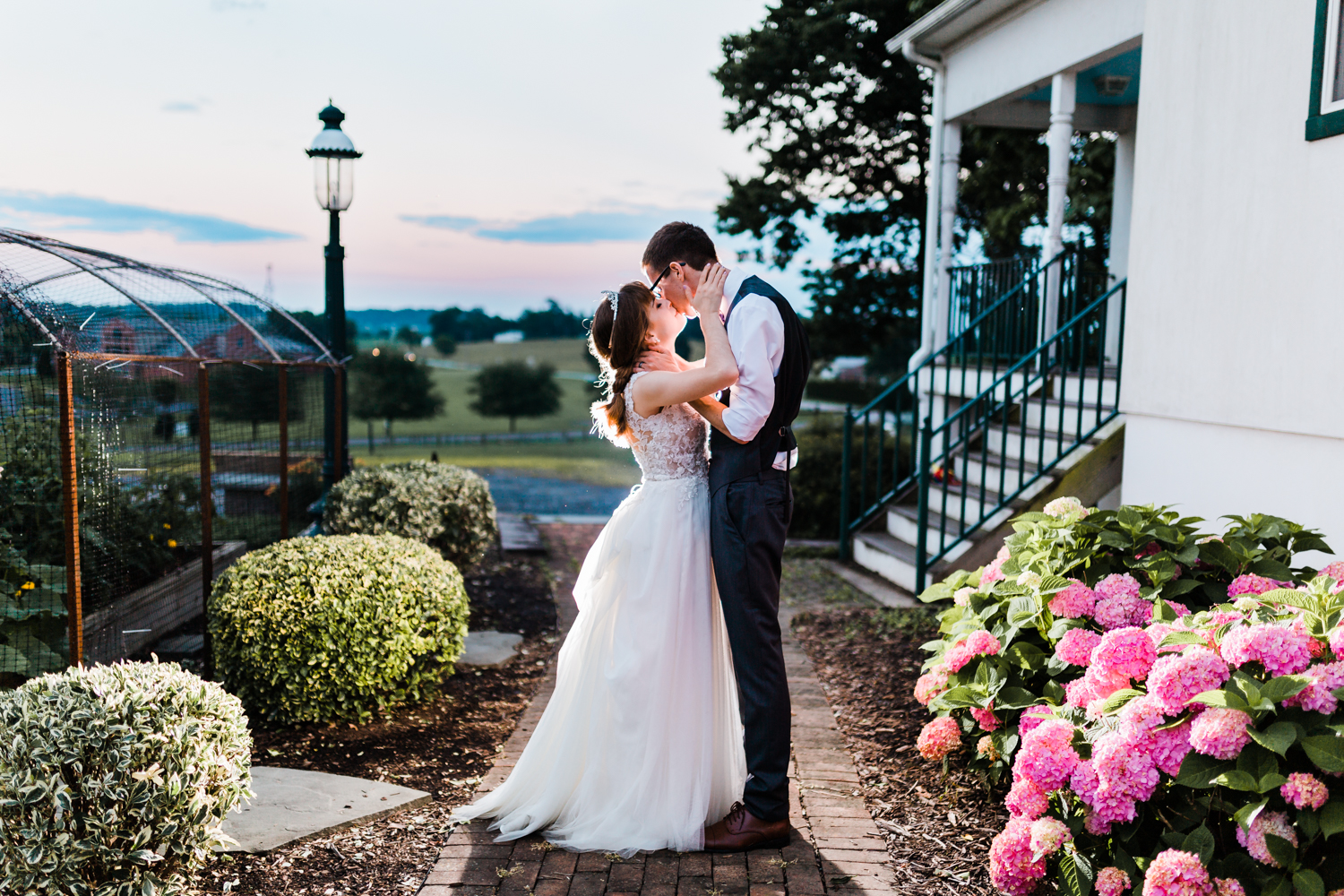 bride and groom kiss during golden hour - top md wedding photographer and videographer