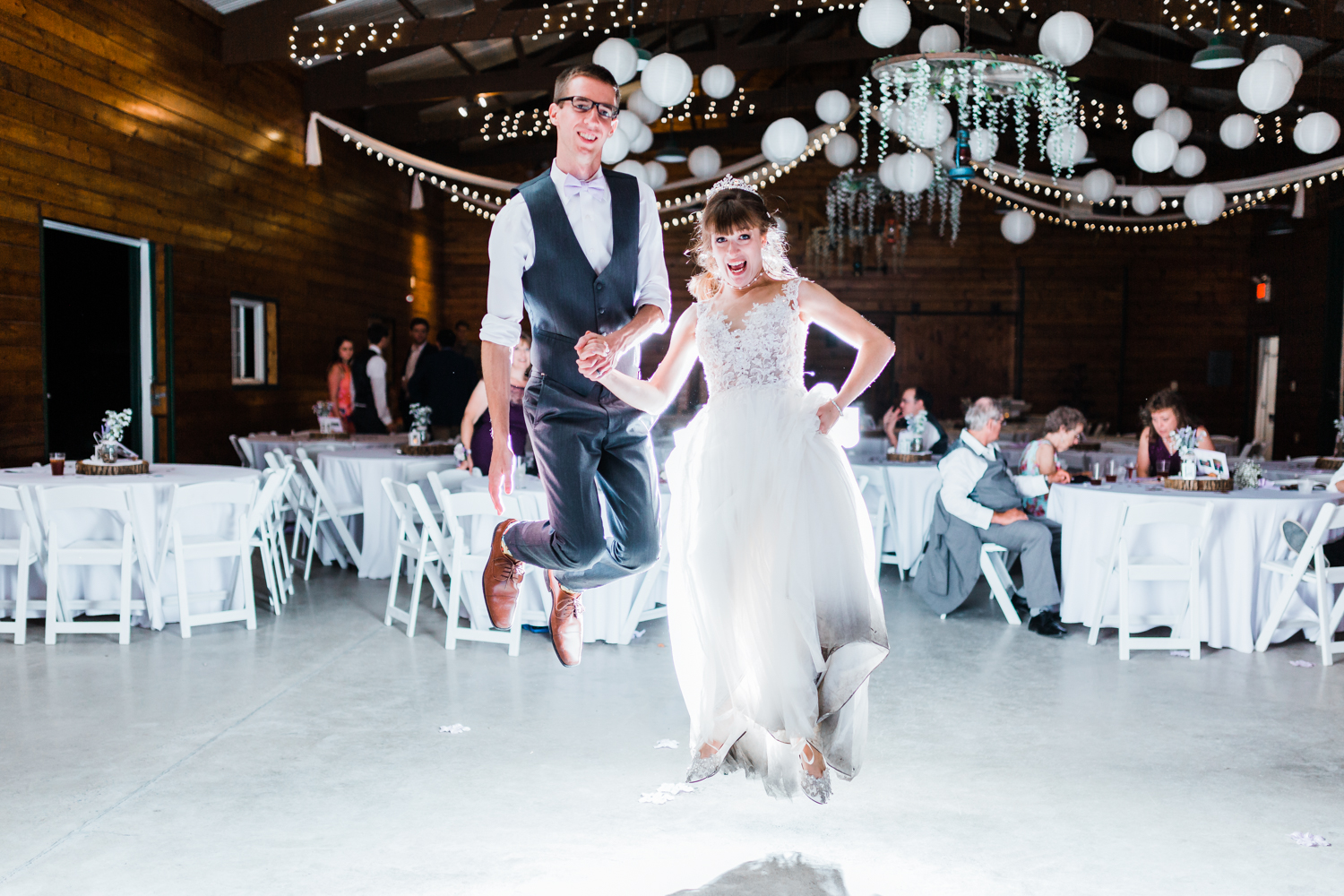 bride and groom jumping together and having fun - night reception - maryland wedding photographer