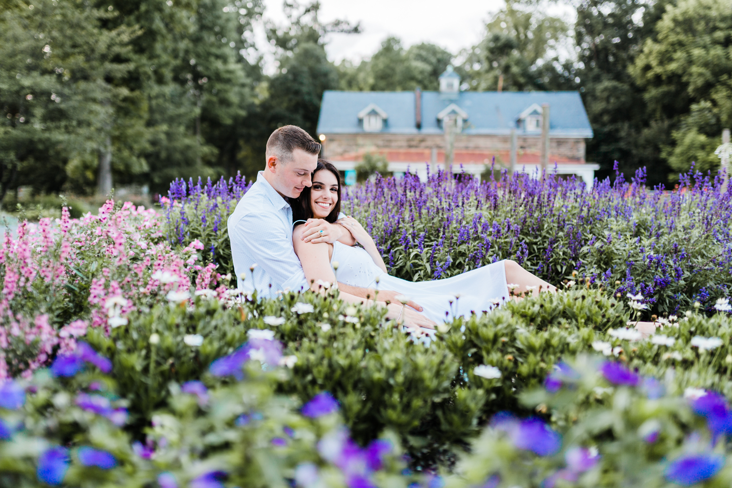 couple snuggling in wildflowers - best maryland engagement photographer
