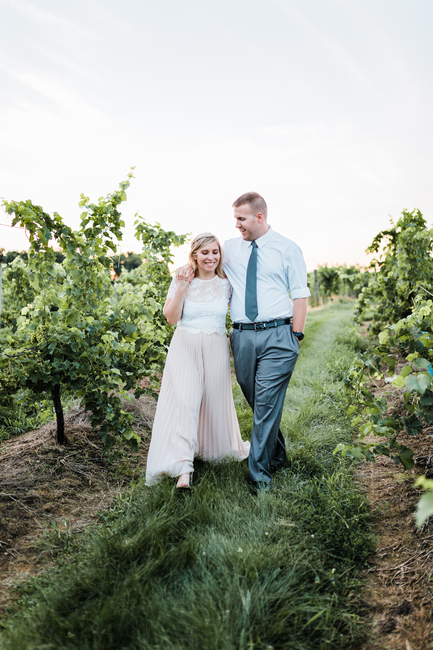 couple walking together during golden hour - winery engagement session inspiration