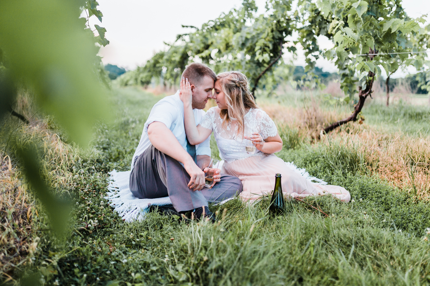 couple snuggled together on picnic blanket with champagne