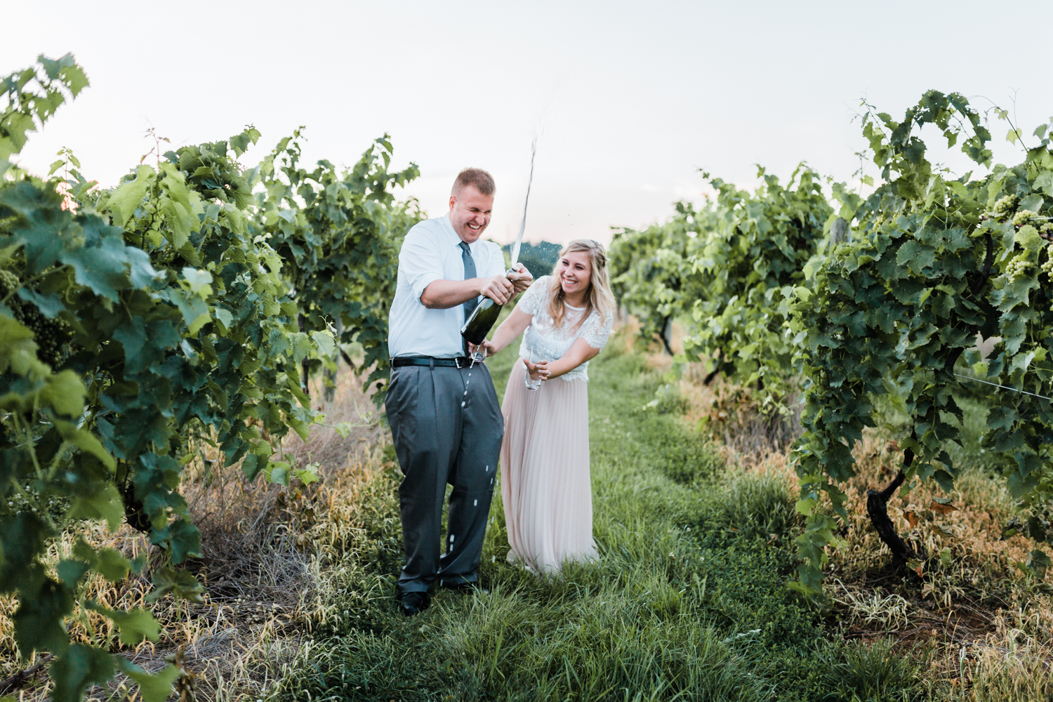 popping champagne during engagement session photos
