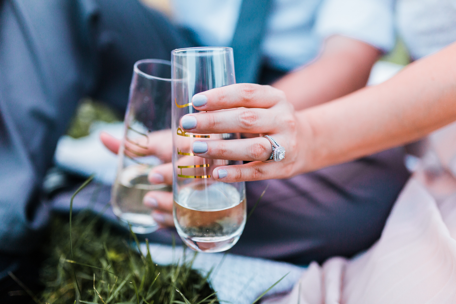 champagne toast engagement session in vineyard with stemless wine glasses