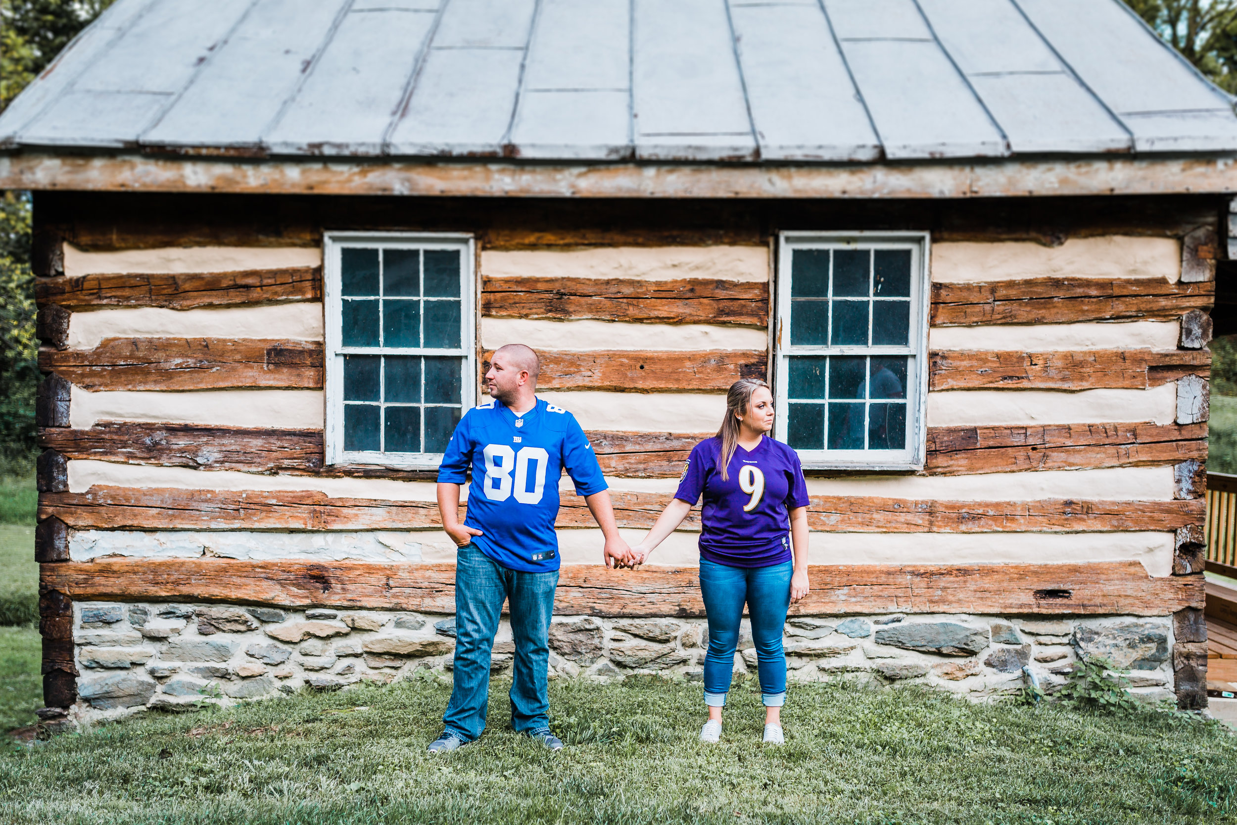 couple in their football gear pose for an engagement photo - best maryland engagement and wedding photographer and cinematographer