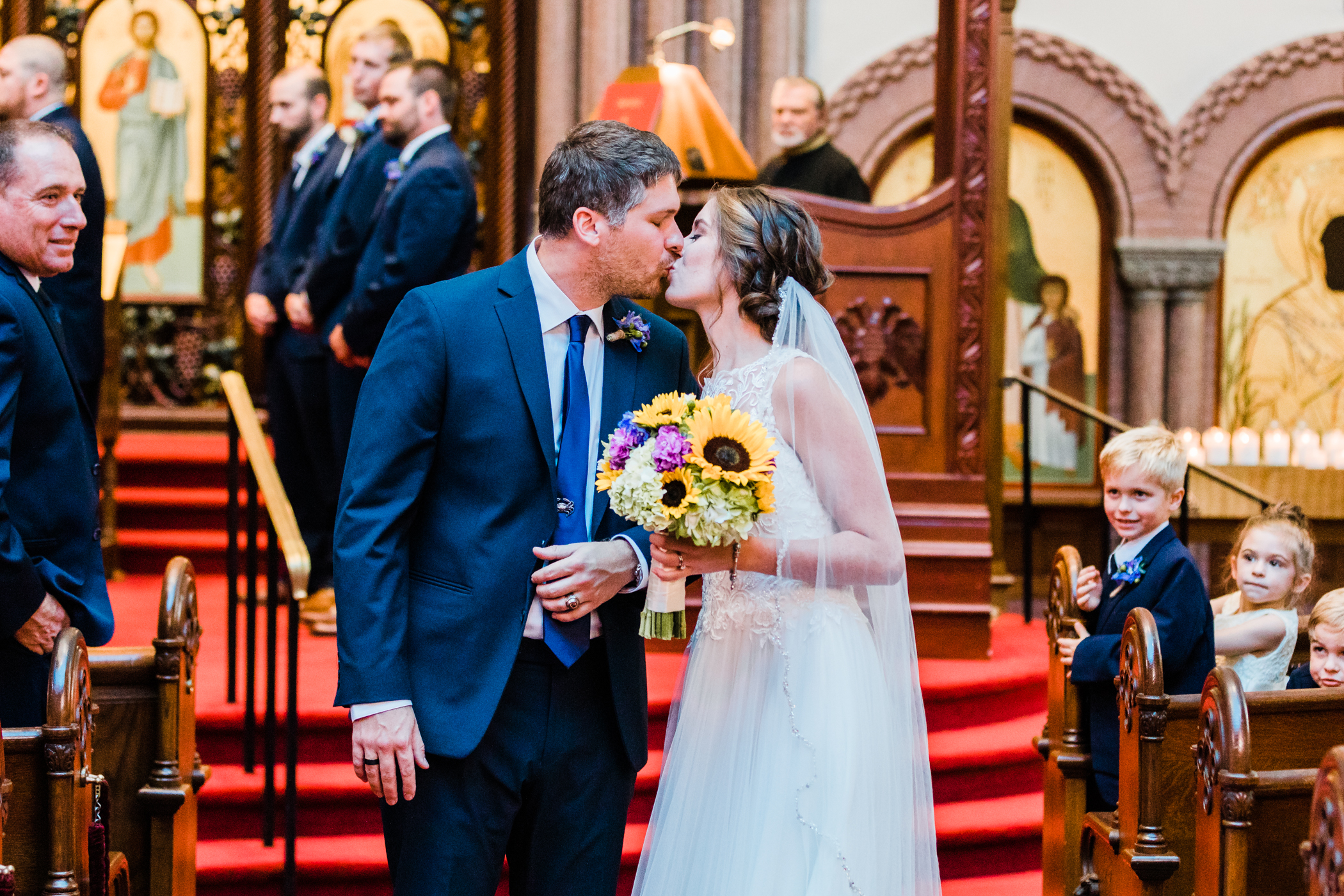 bride and groom first kiss - greek orthodox wedding
