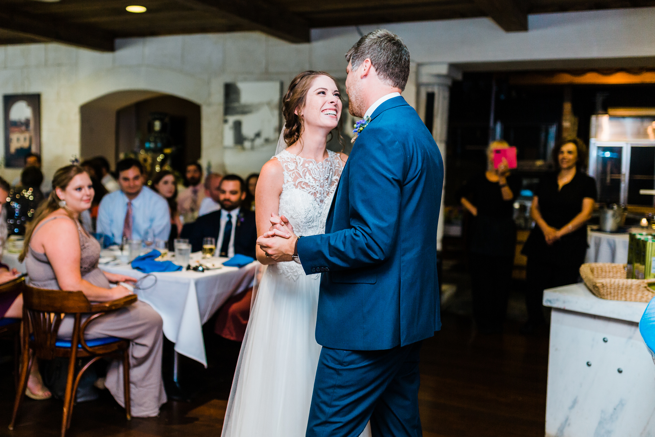 bride and groom laugh during their first dance at greek restaurant in baltimore, maryland