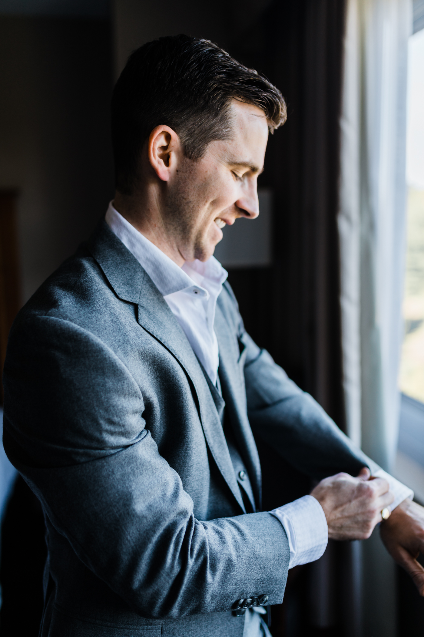 groom putting on his watch while getting ready in a hotel - MD wedding Photographer
