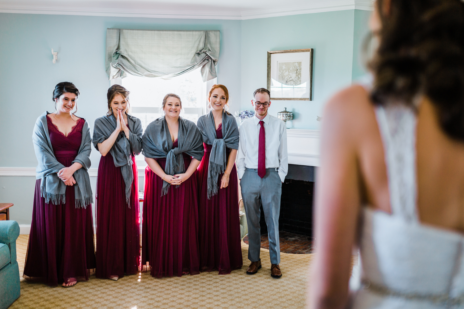 bride showing her bridesmaids and groomsman for the first time