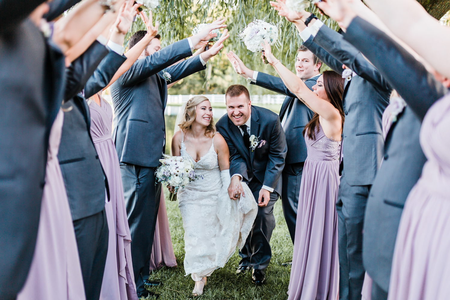 Bride and Groom running with cheering wedding party - Maryland rustic wedding