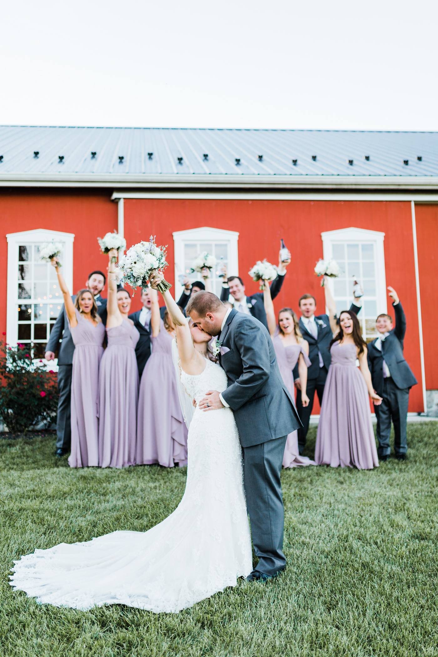 Wedding party cheers as bride and groom kiss - rustic wedding venue in Maryland