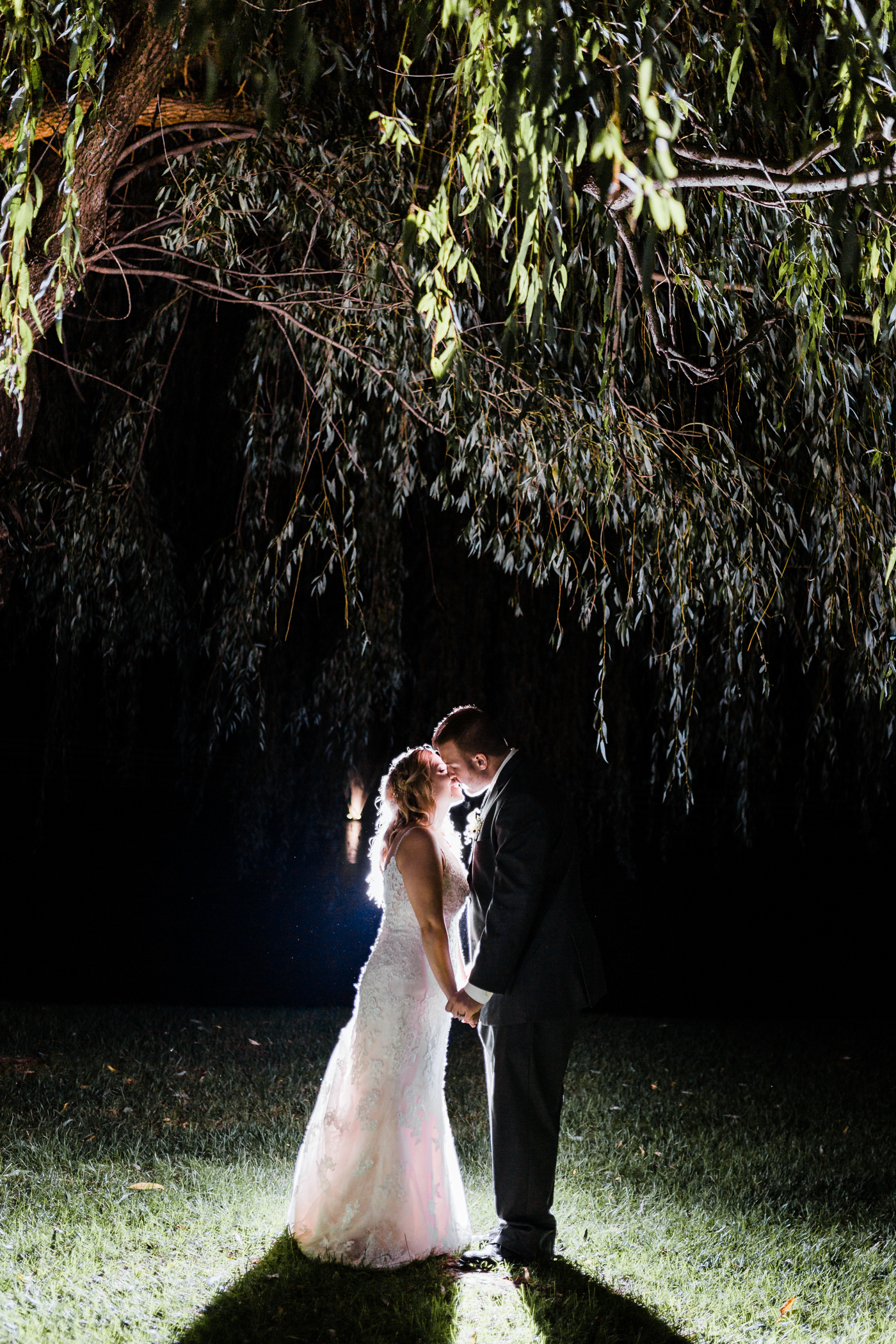 romantic night portrait of bride and groom under willow tree at Pond View Farm
