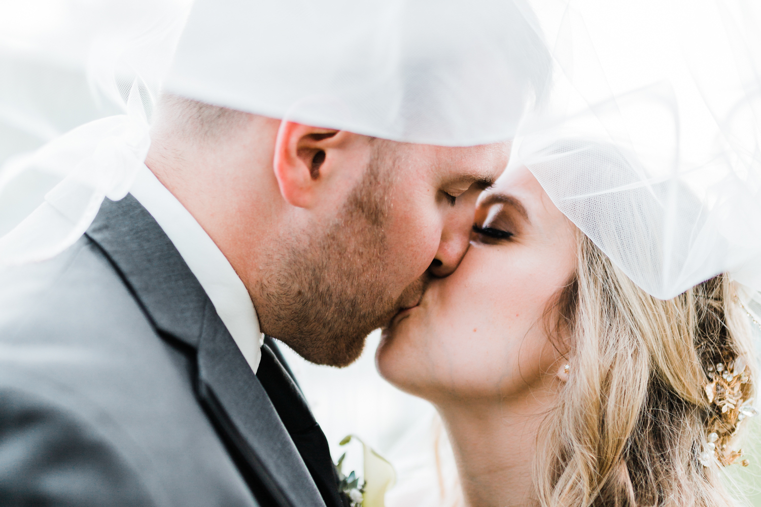 bride and groom kiss under veil - romantic wedding photographer in Maryland
