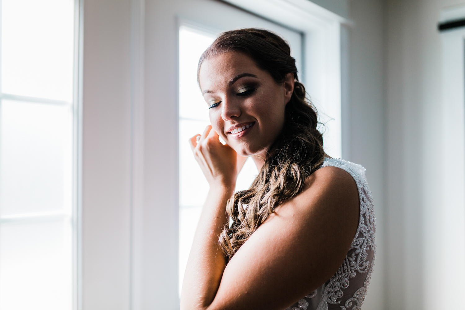 Bride putting ear rings in by window - highly rated videographer in Maryland