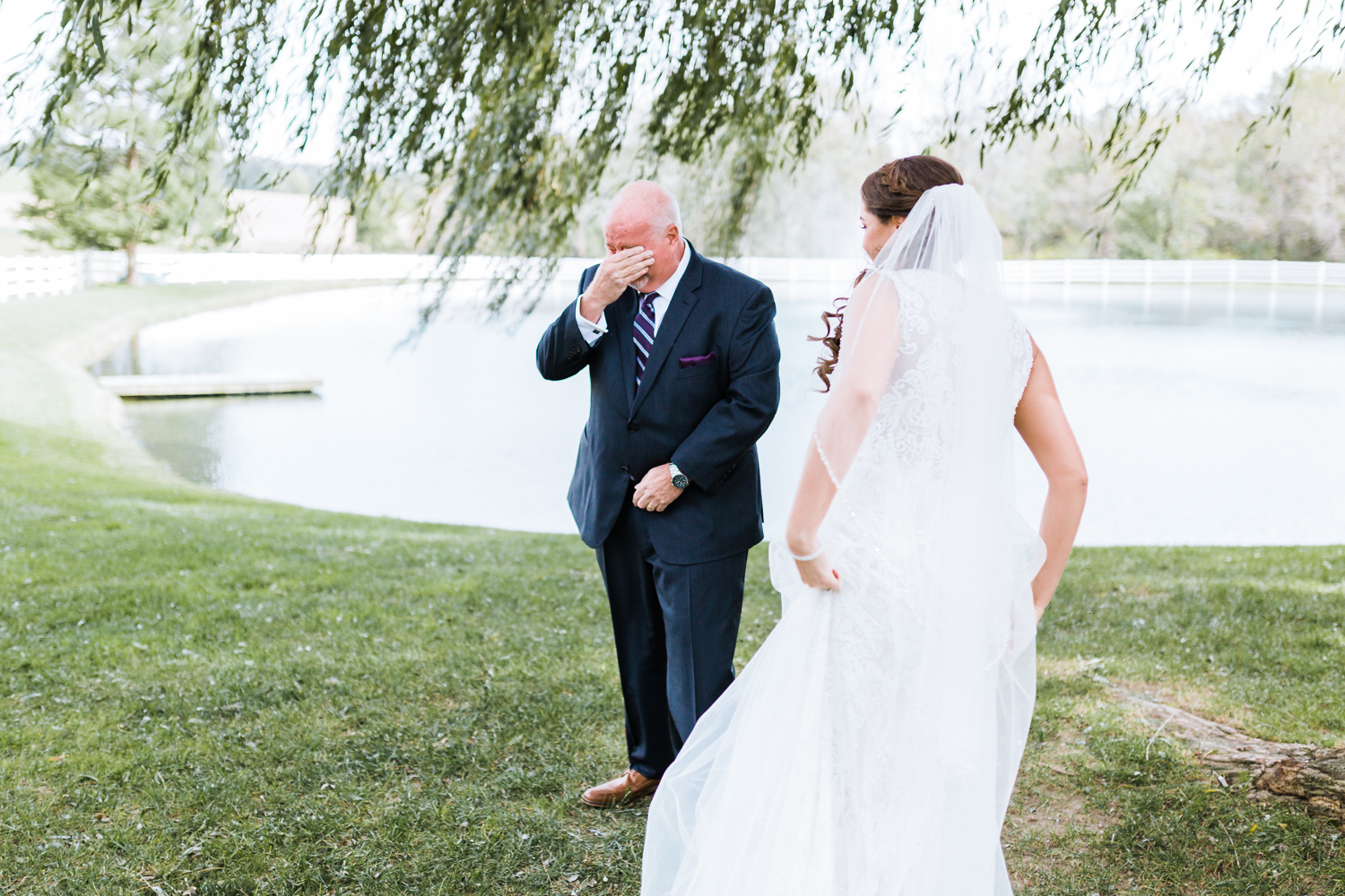 adorable moment between father and daughter during their first look - Maryland wedding venues with pond or water and willow trees