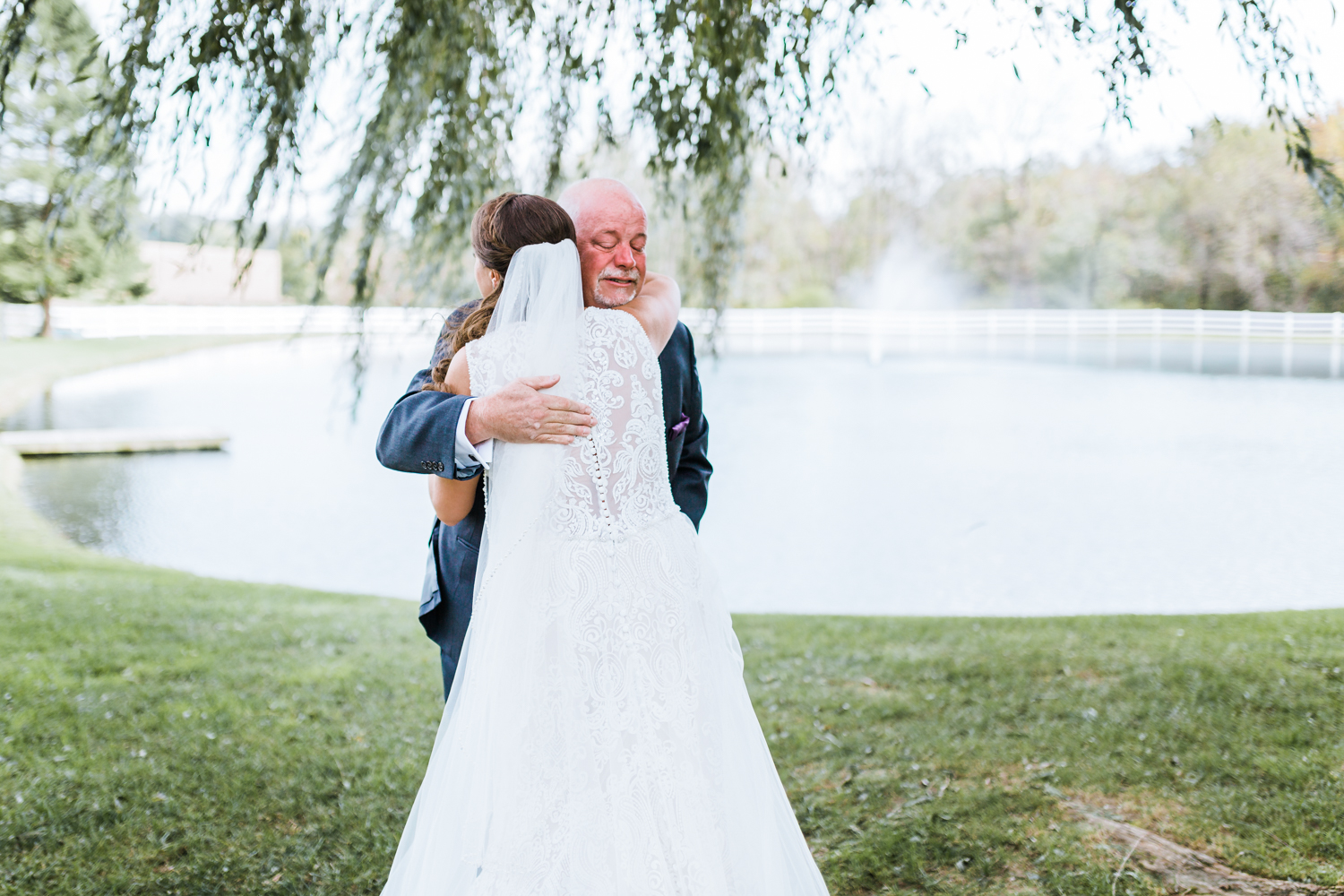 father and bride hug during their first look - Pond View Farm Weddings - best wedding photographer and videographer in Maryland