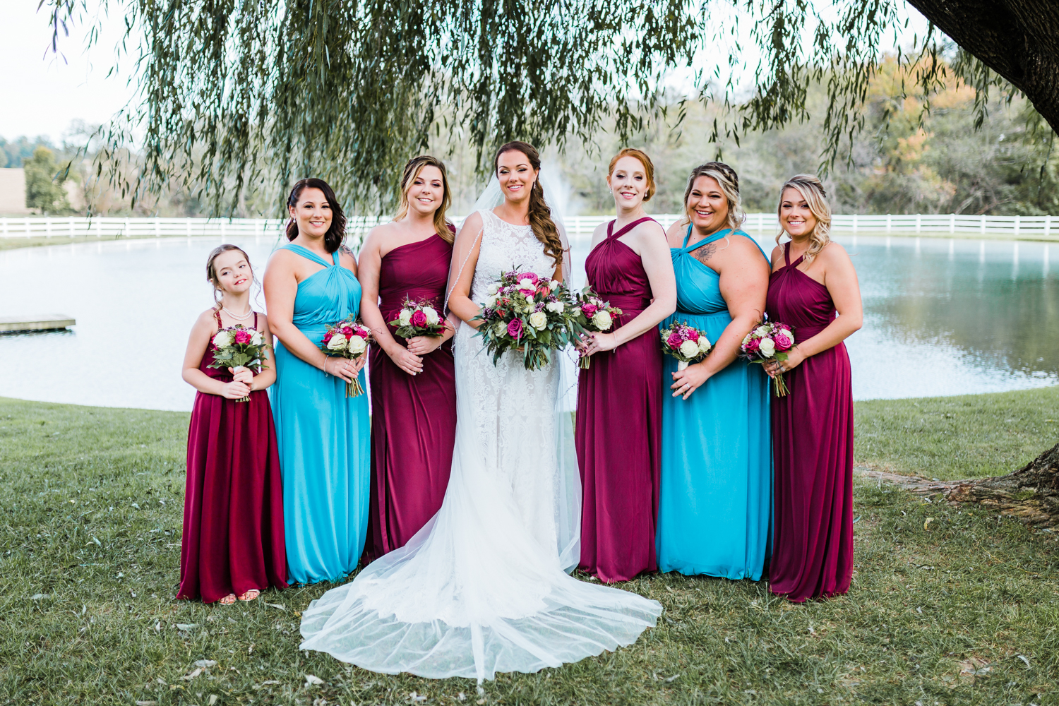 bride and her bridesmaids under the willow tree at Pond View Farm - red and blue wedding color schemes