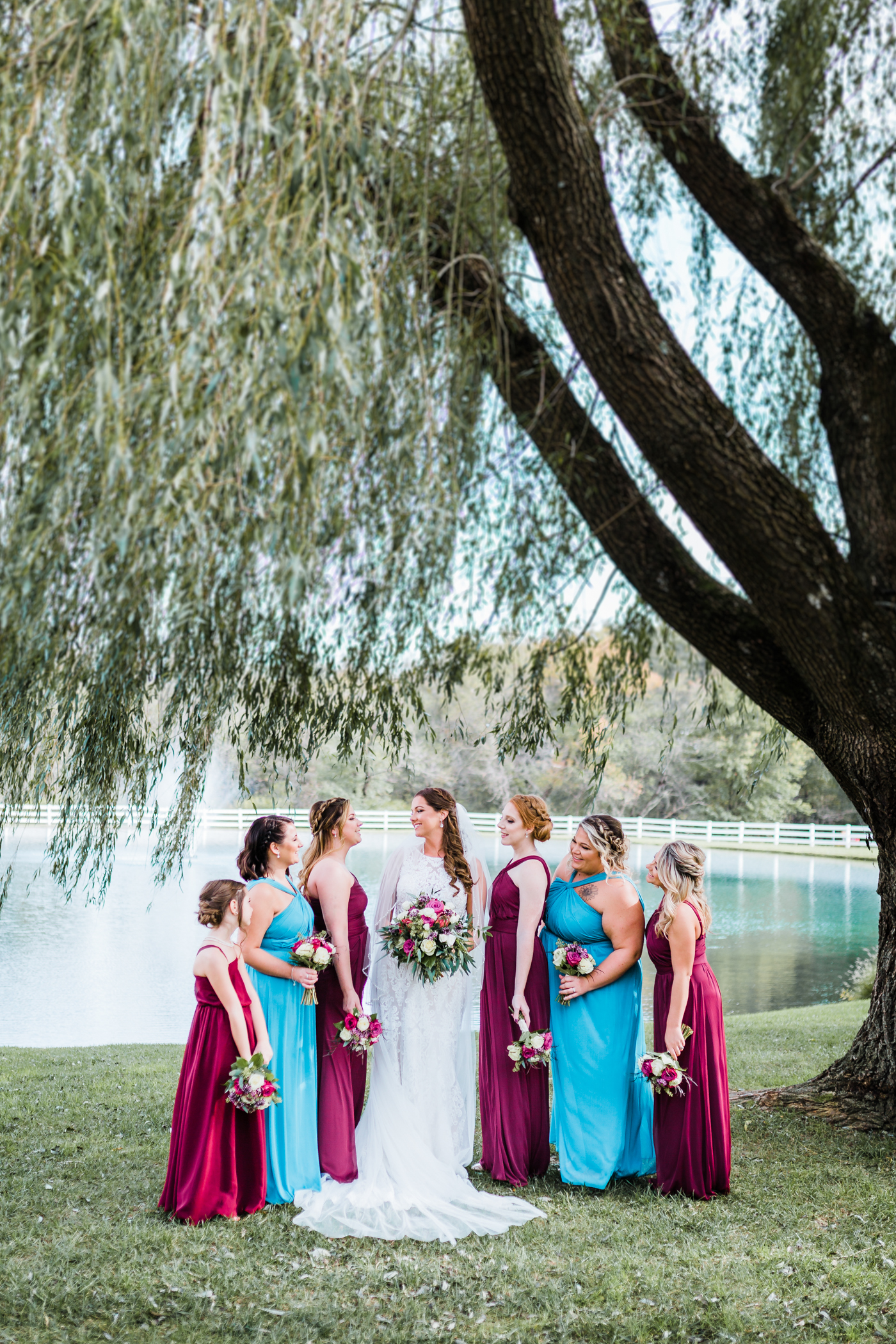 Bride with her bridesmaids at Pond View Farm - red and blue wedding color scheme