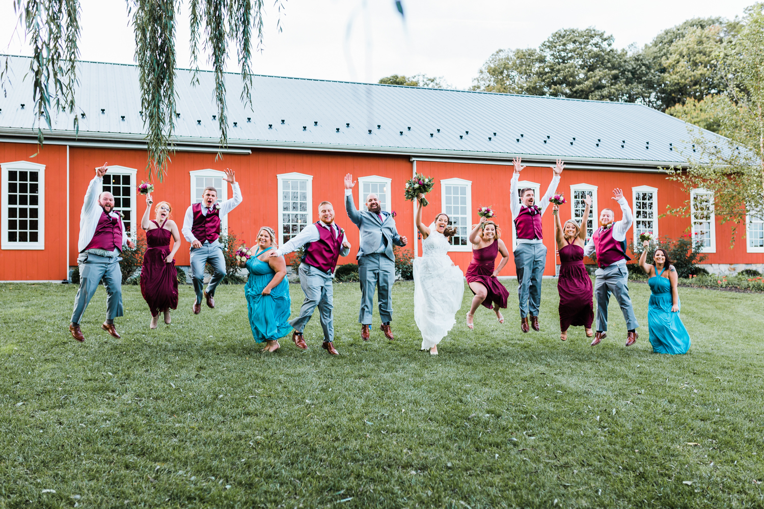 Bridal party jumping together and having fun at Pond View Farm - top rated MD wedding photographer and cinematographer