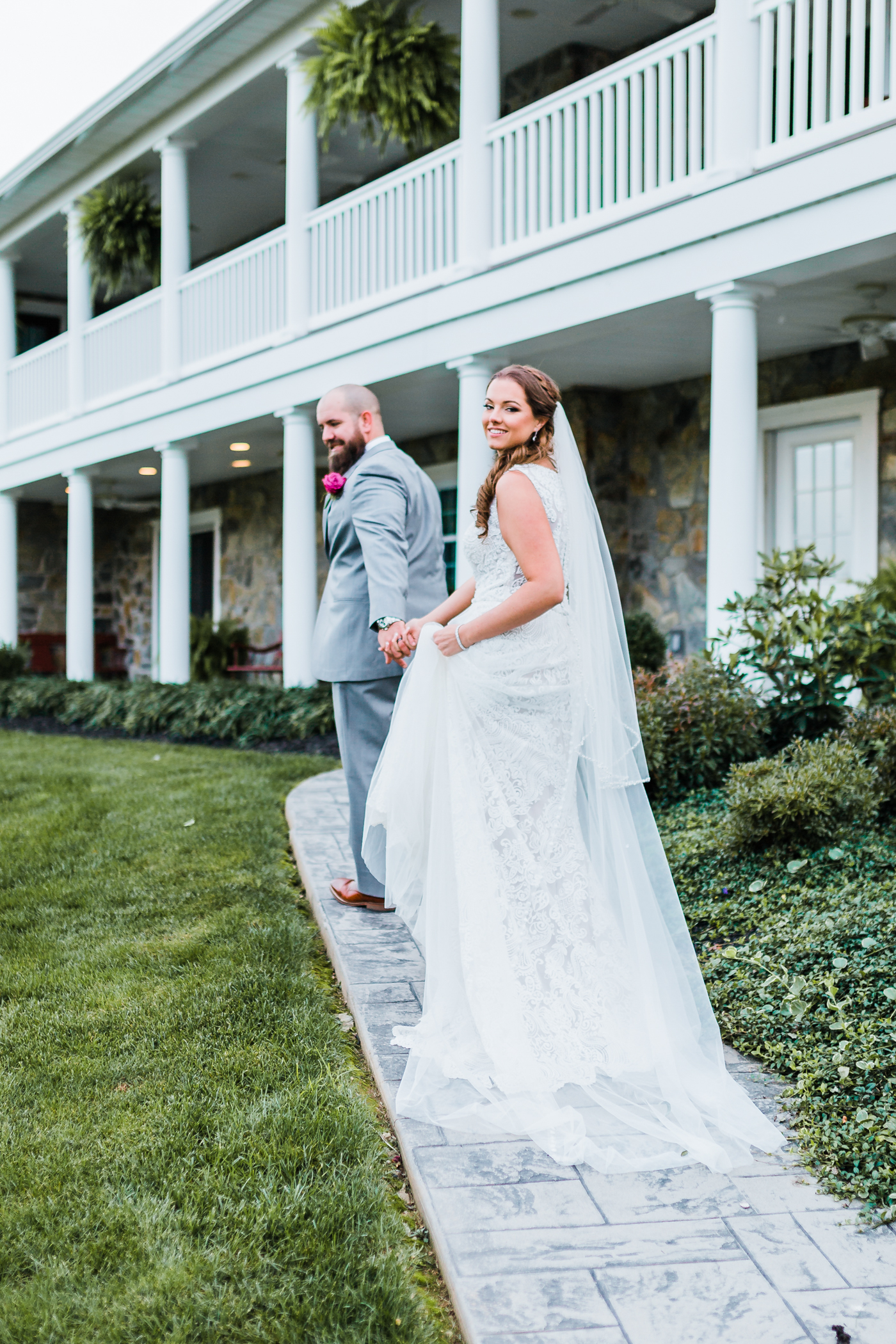 bride smiles back as she walks away with her groom - Maryland wedding photographer