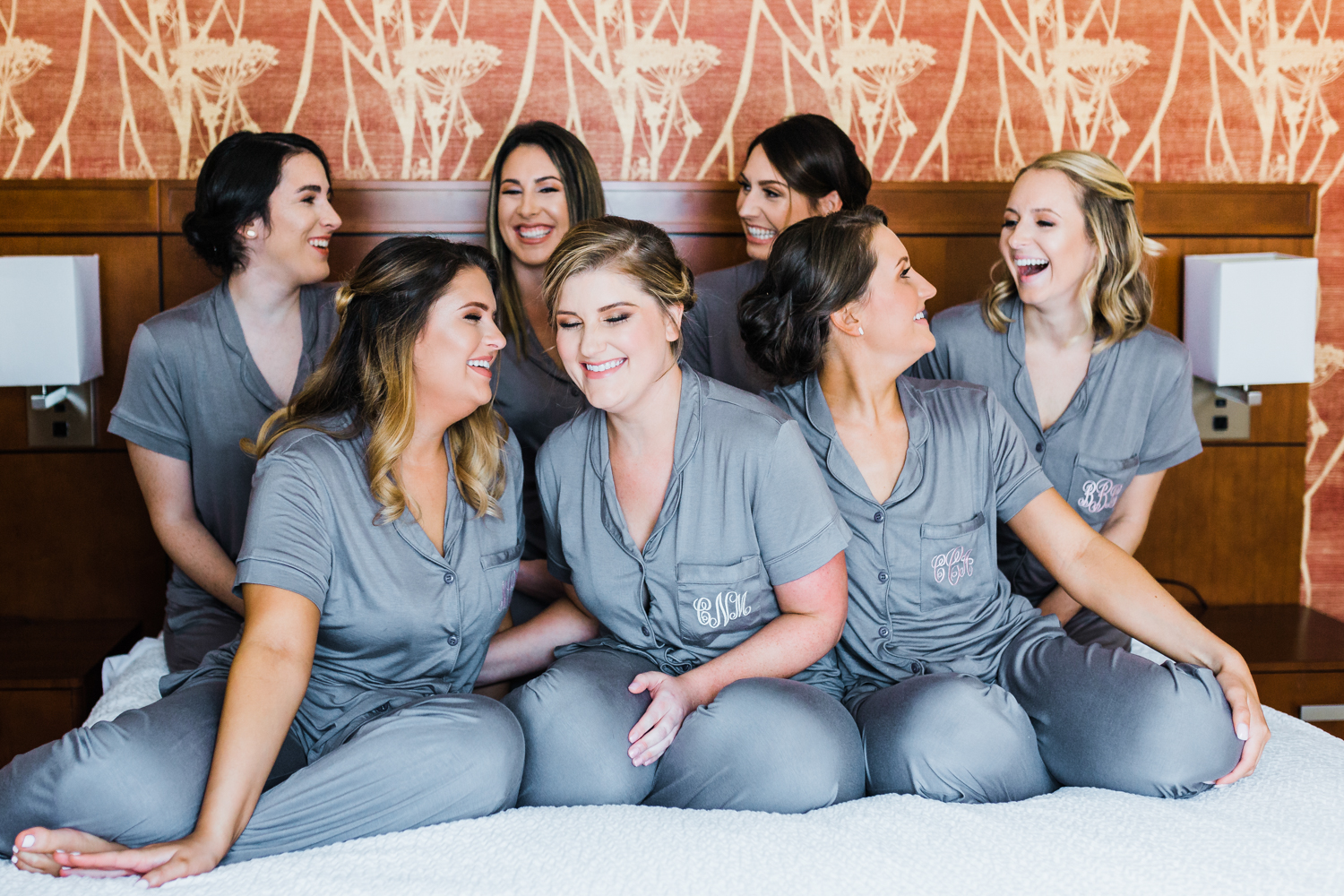 bride laughing with her bridesmaids on a bed in a hotel - Maryland wedding venues in downtown Frederick