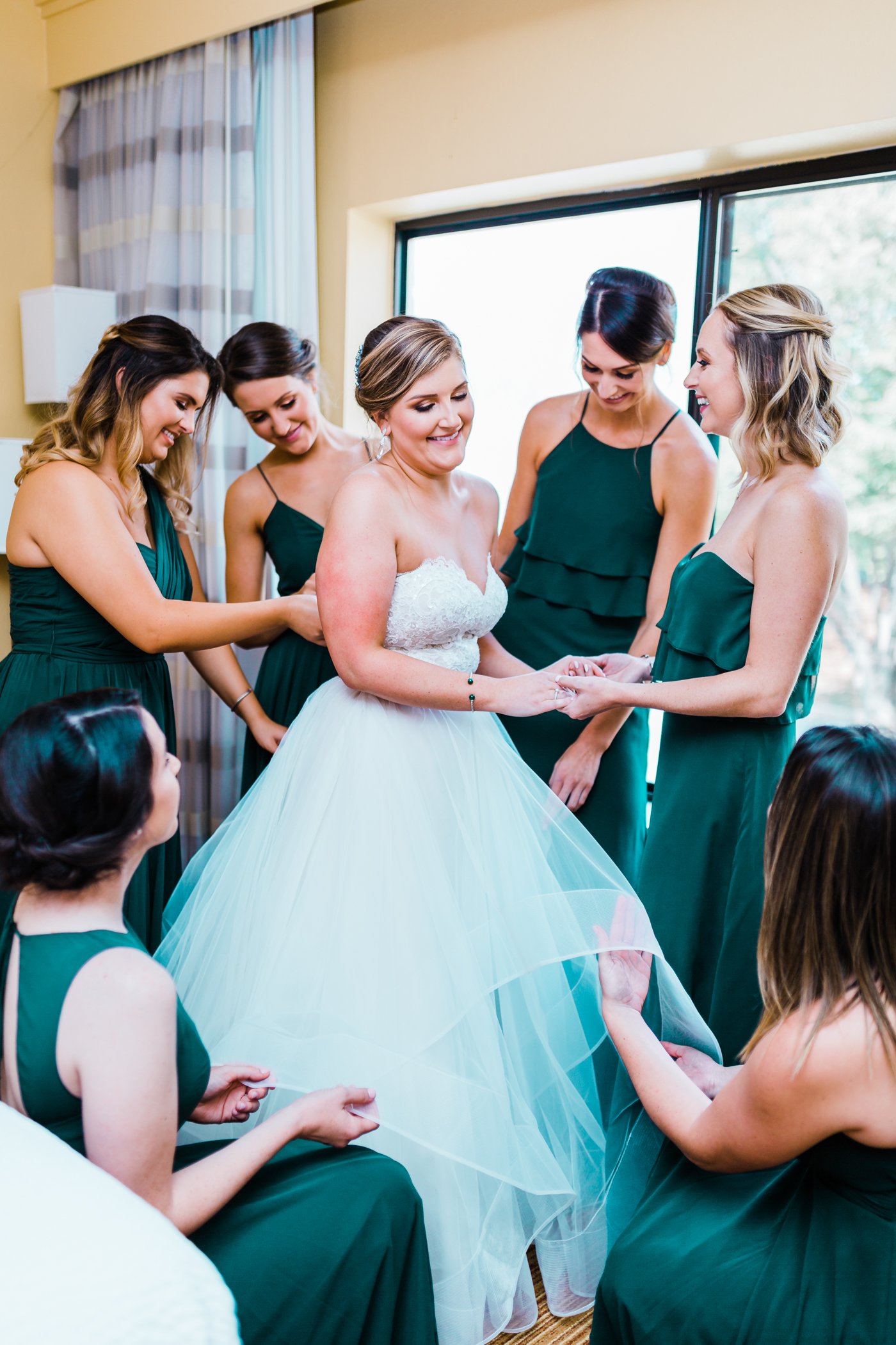 bride laughing while she gets ready in her hotel room - Maryland wedding photographer