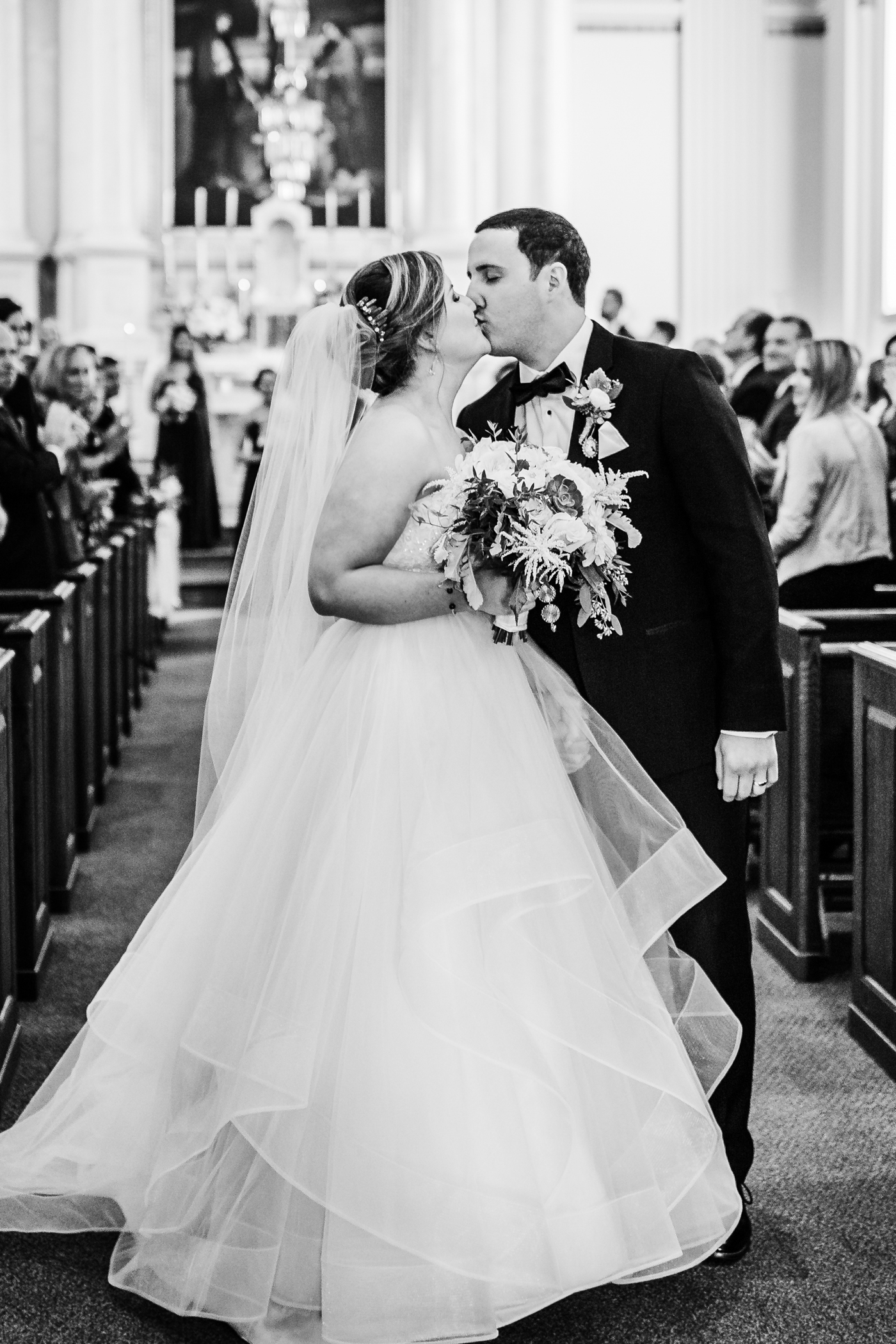 bride and groom kiss as they come down the aisle - catholic wedding ceremony inspo