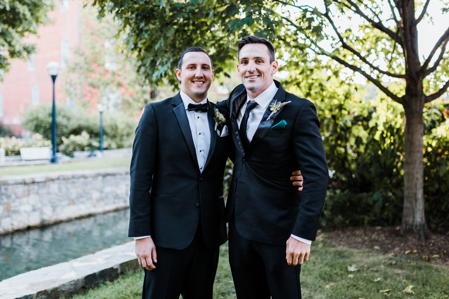 groom poses with his brother along Carroll Creek in Frederick, MD