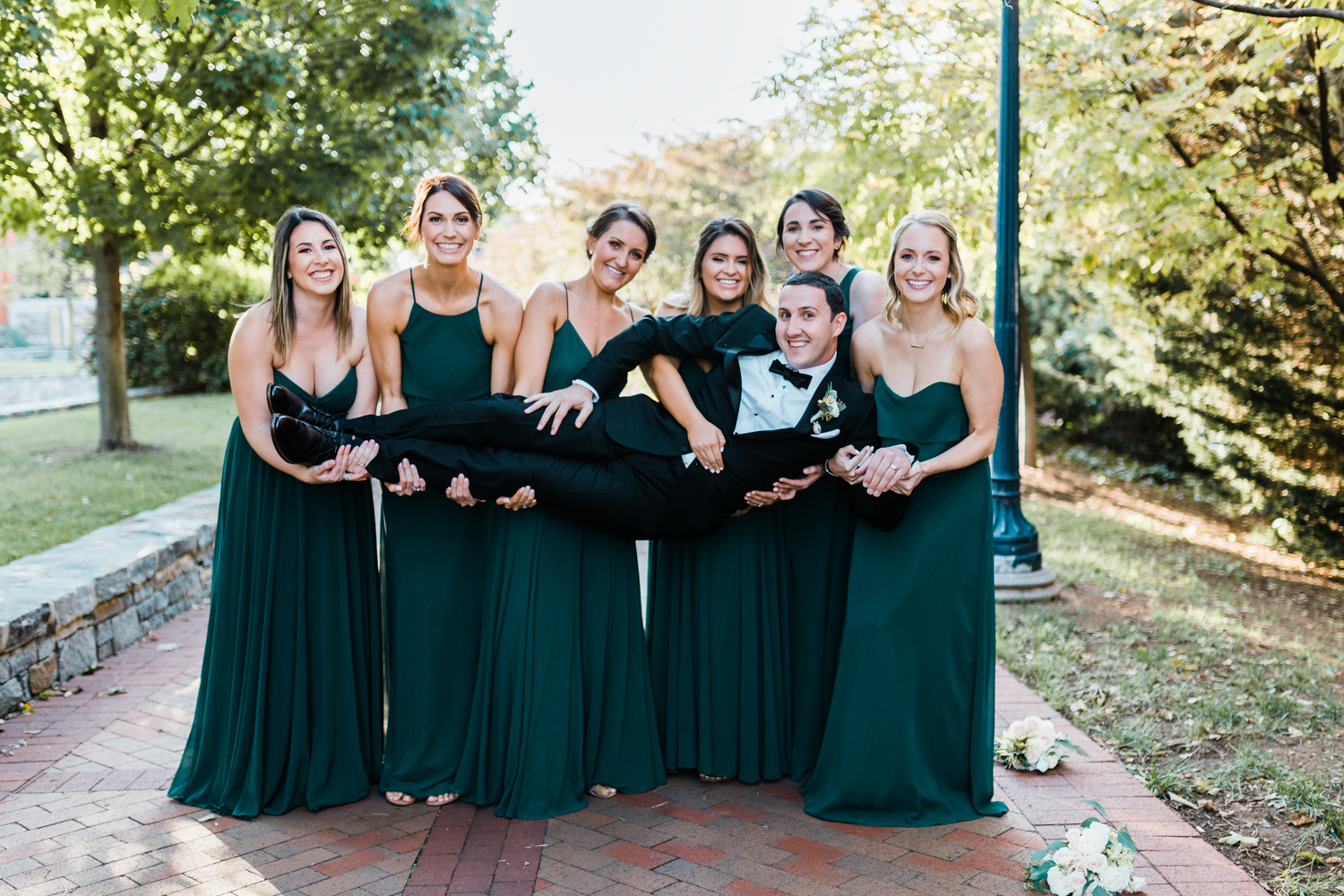 bridesmaids hold groom for a funny photo