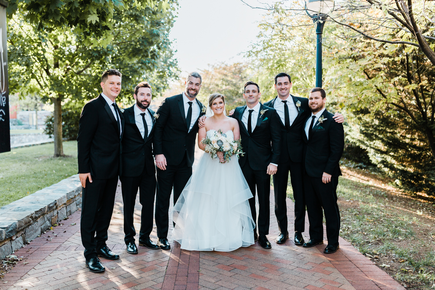 bride poses with the groomsmen - bridal party ideas