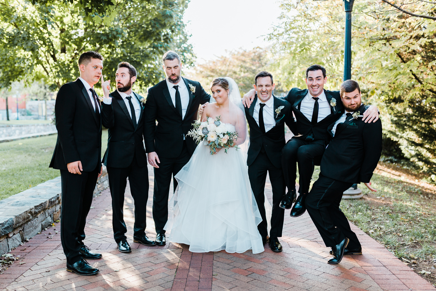 bride and groomsmen share a funny photo - McClintock Distilling wedding