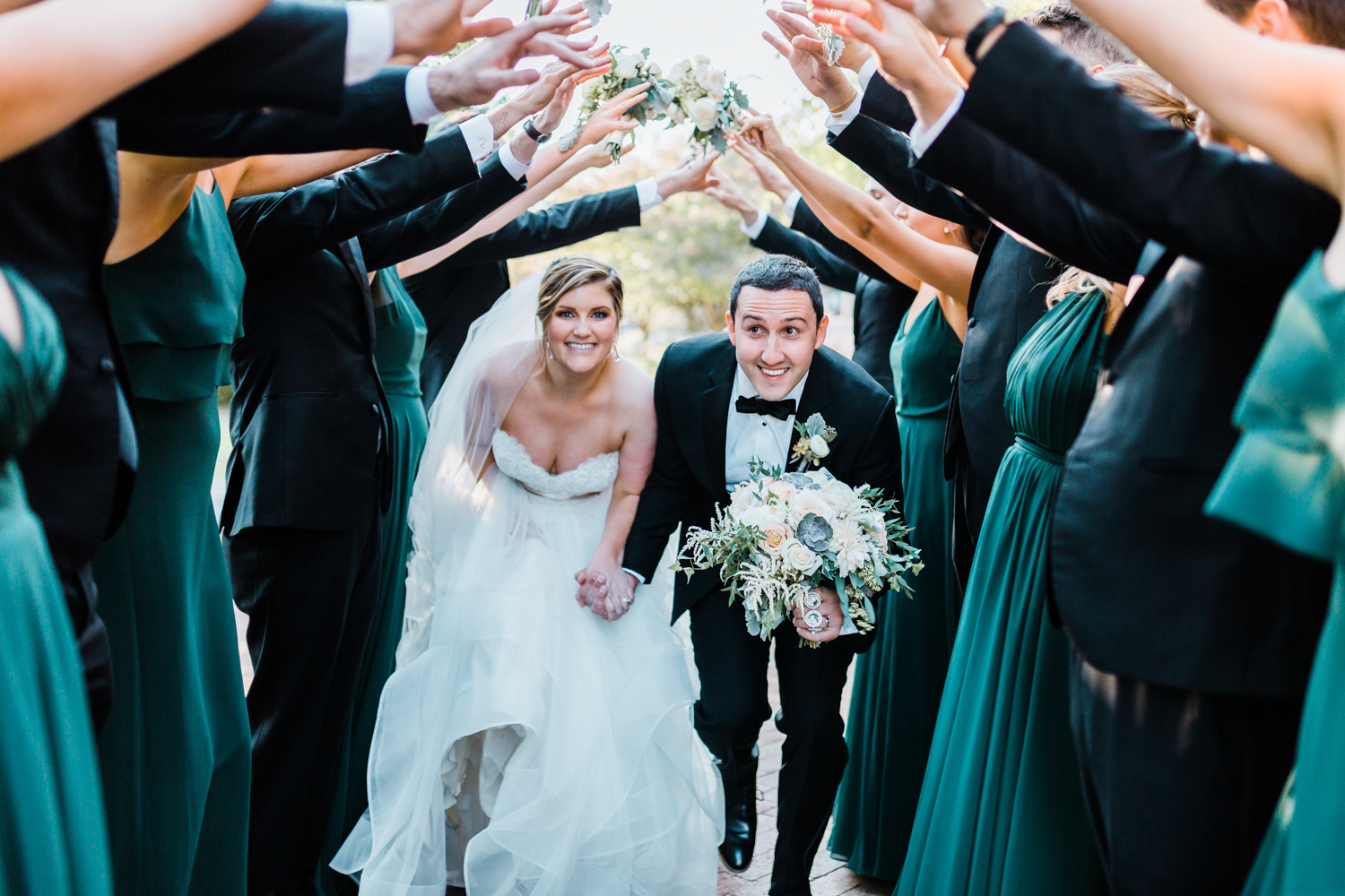 Bride and Groom run through the middle of their bridal party - fun shots to do with your bridal party - Maryland husband and wife based wedding photographers