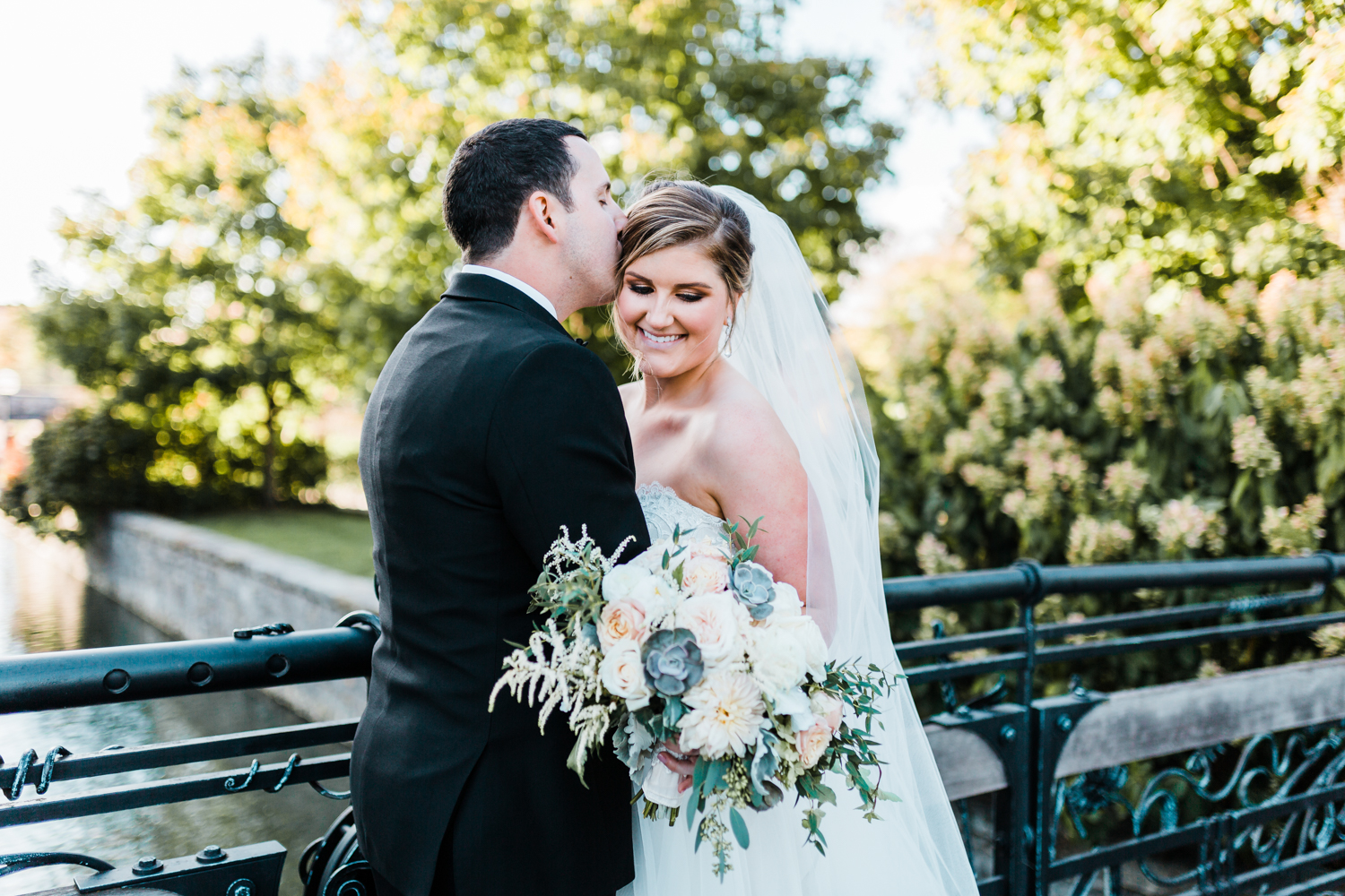 beautiful bride and her groom on the bridge across from McClintock Distilling with her succulent and dahlia bouquet - Maryland wedding inspiration
