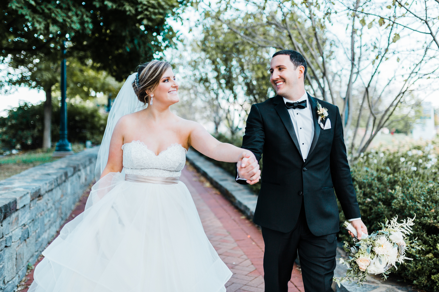 happy couple walking together and smiling - top rated wedding photographer and videographer in Maryland