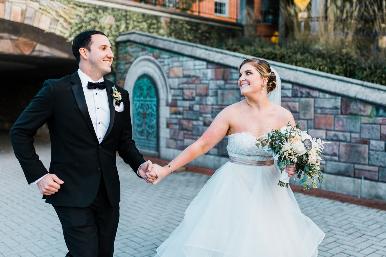 bride and groom running together and laughing in downtown Frederick Maryland