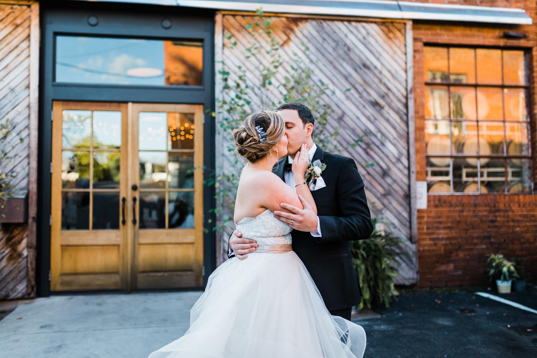 bride and groom kiss outside of McClintock Distilling