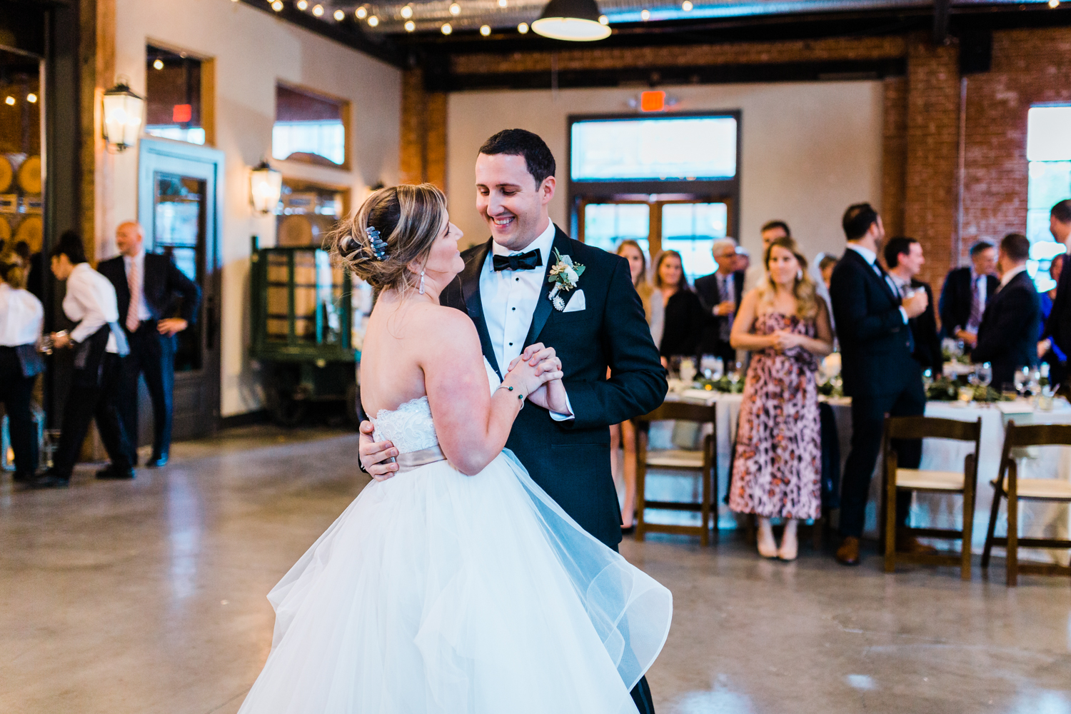 Bride and groom smiling at each other during first dance - top photographer in MD