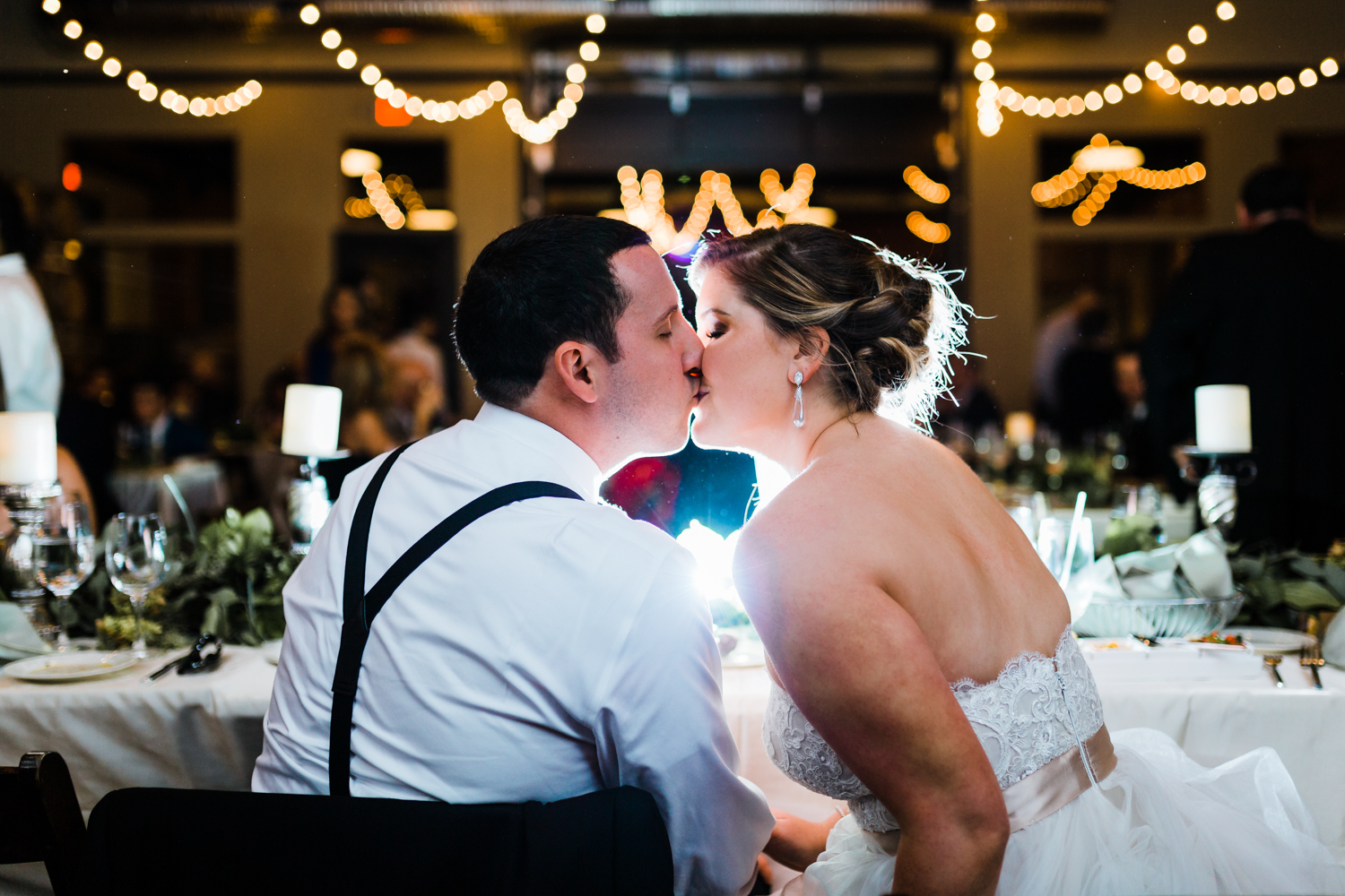 Newly weds kiss at head table - top rated photographer in Frederick Maryland