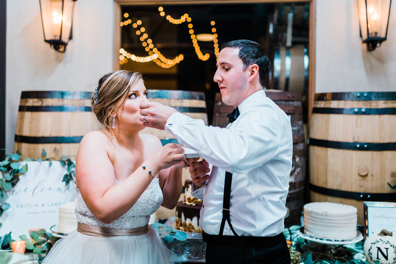 groom feeds bride wedding cake - industrial and modern wedding venue McClintock Distilling in Frederick MD