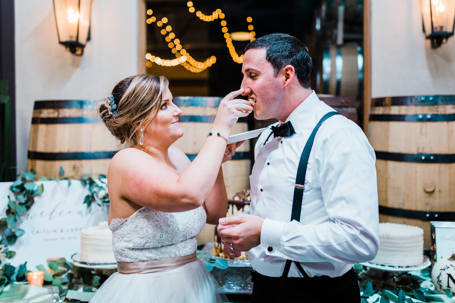 Bride feeds wedding cake to groom - beautiful and classic wedding at Frederick MD McClintock distillery