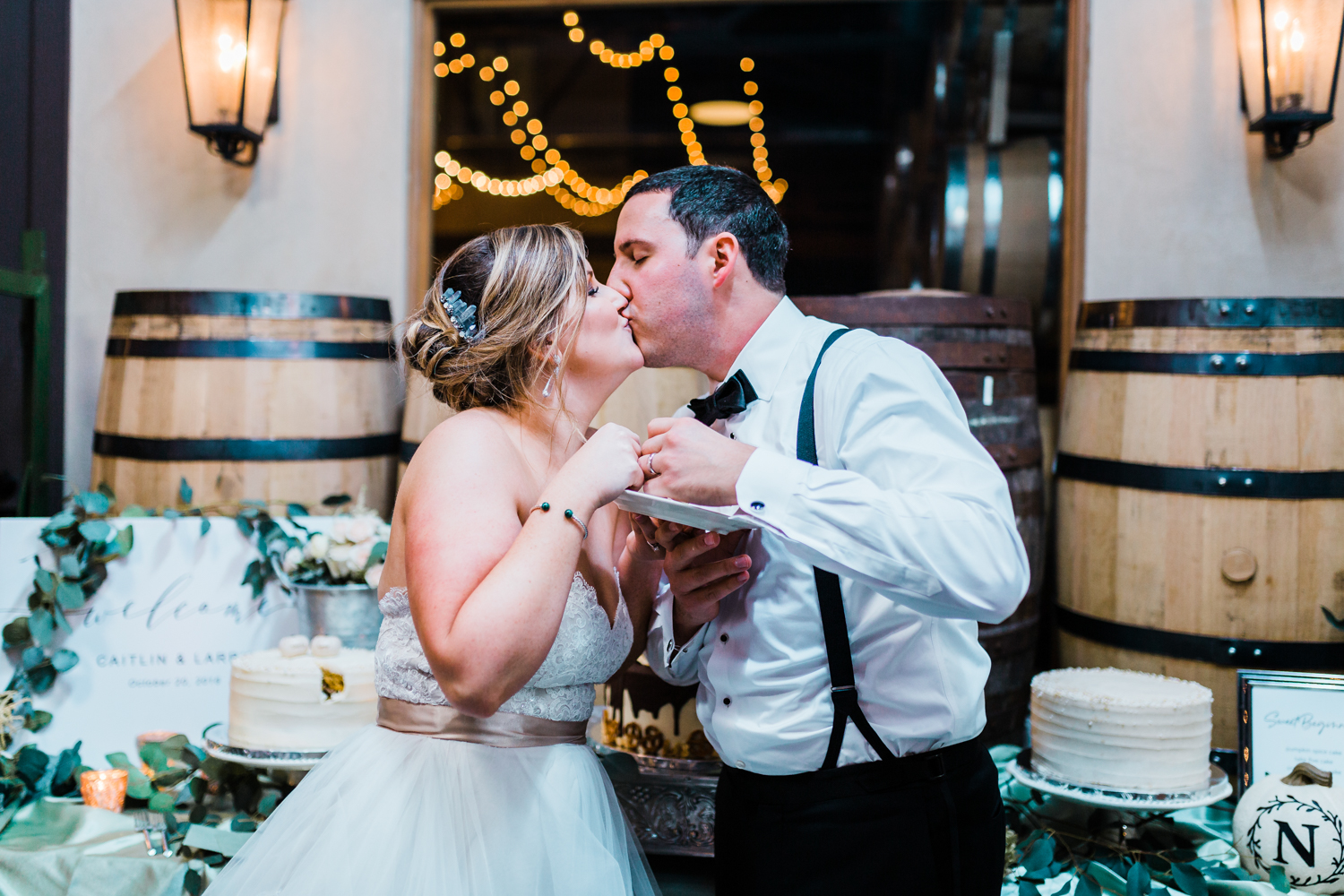 Bride and groom kiss after cutting their wedding cake - candid wedding photographers in Maryland